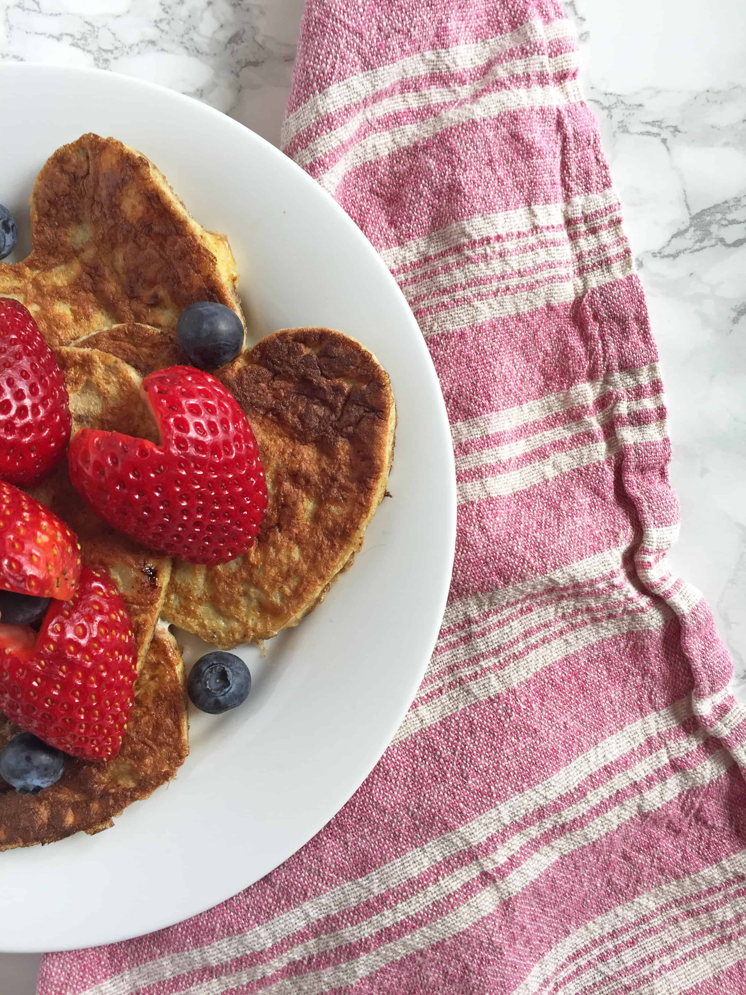 3 ingredient heart pancakes with strawberries and blueberries.