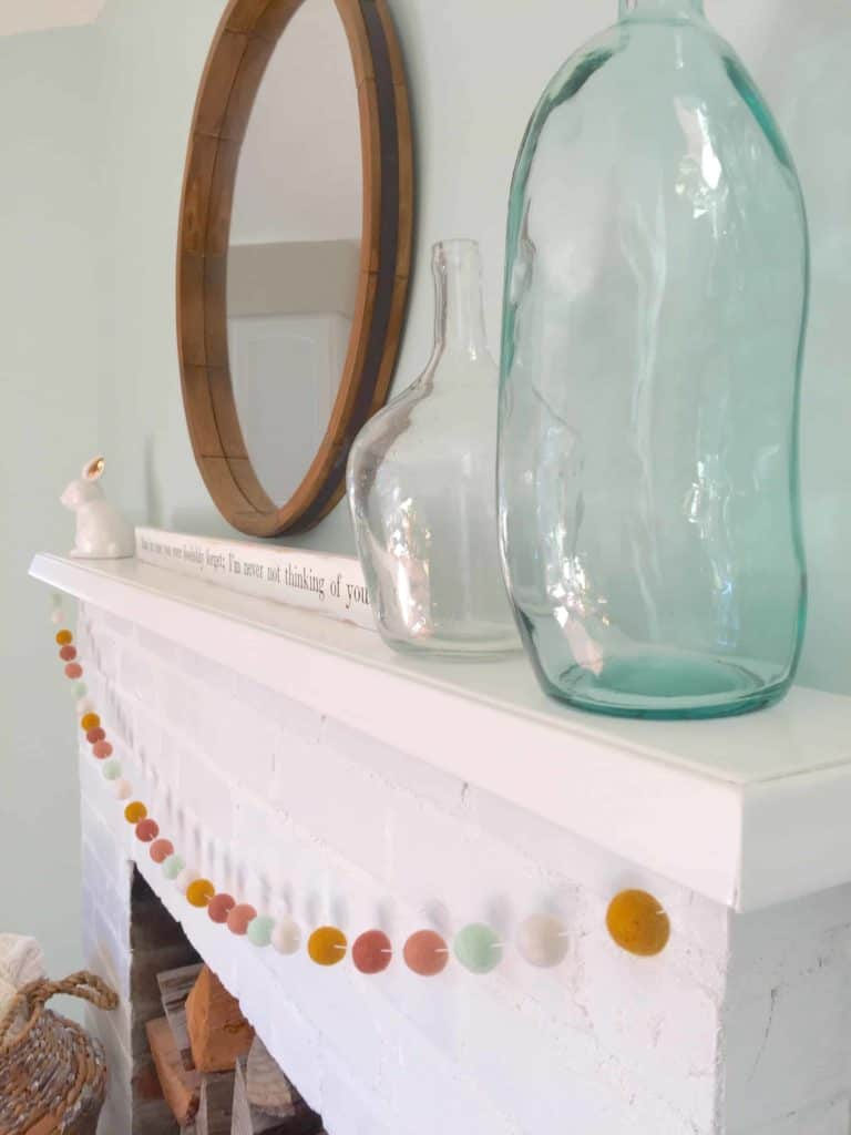 white painted brick fireplace with aqua glass jars and white ceramic bunny