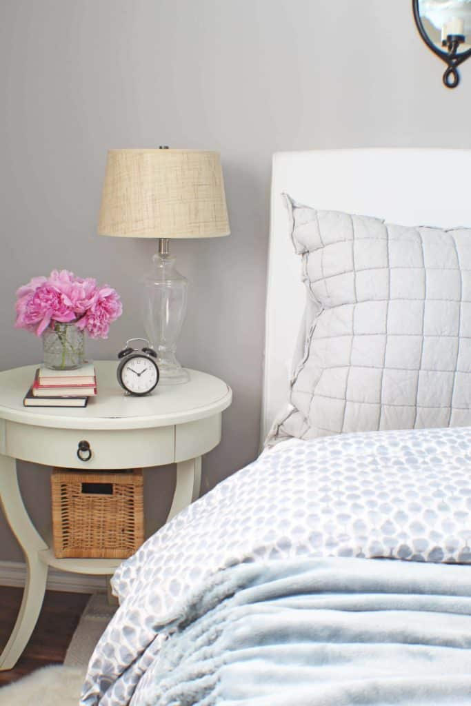 white upholstered headboard and blue west elm bedding