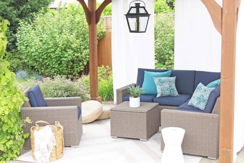 Summer is just around the corner, which means longer days and more outdoor time. Are you stuck on where to start with your outdoor space? Try these 5 simple patio makeover ideas. #summerpatio #outdoorspace #outdoorlanterns #pergola #wickersectional #outdoorcurtains #outdoorrug #summerentertaining #outdoorlivingroom #bluedecor #aquadecor #backpatio #backyard #backdeck #smallyard