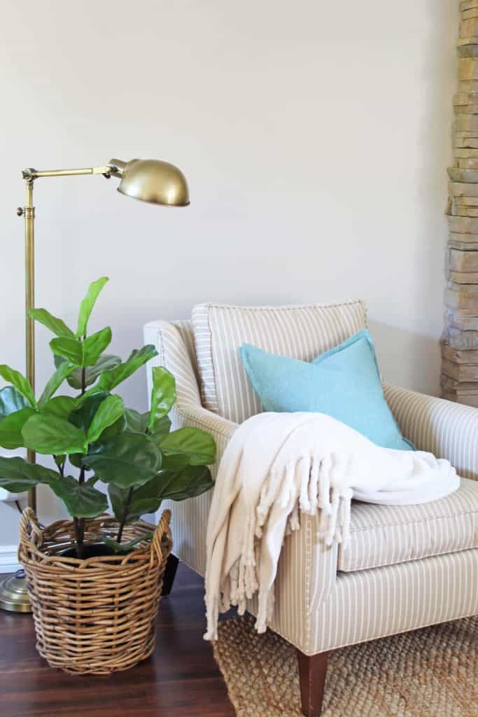 pottery barn chair with fiddle leaf fig and brass lamp