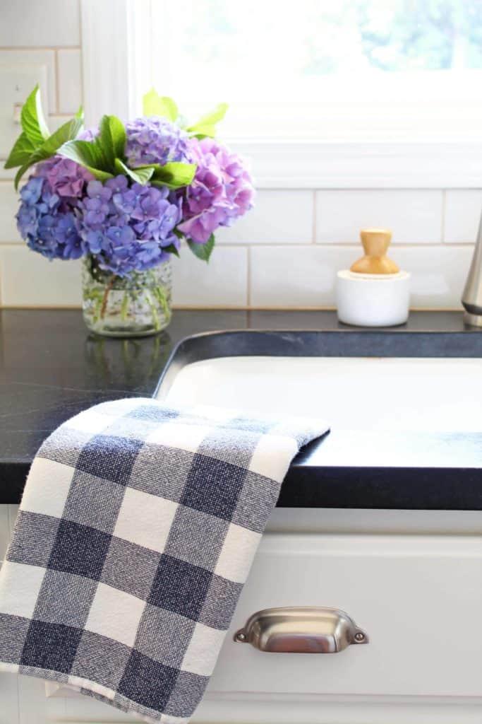 farmhouse kitchen sink with soapstone counter and hydrangeas