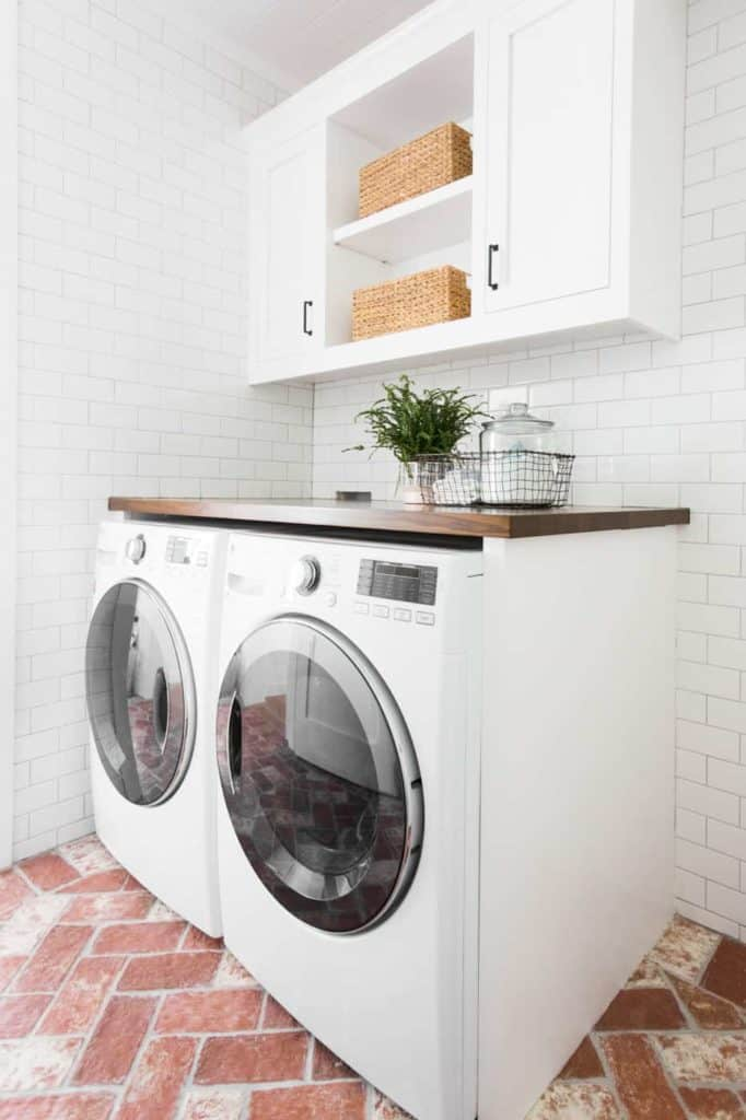 subway tile and brick laundry room