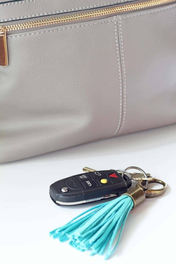 gray purse backpack with turquoise tassel keychain