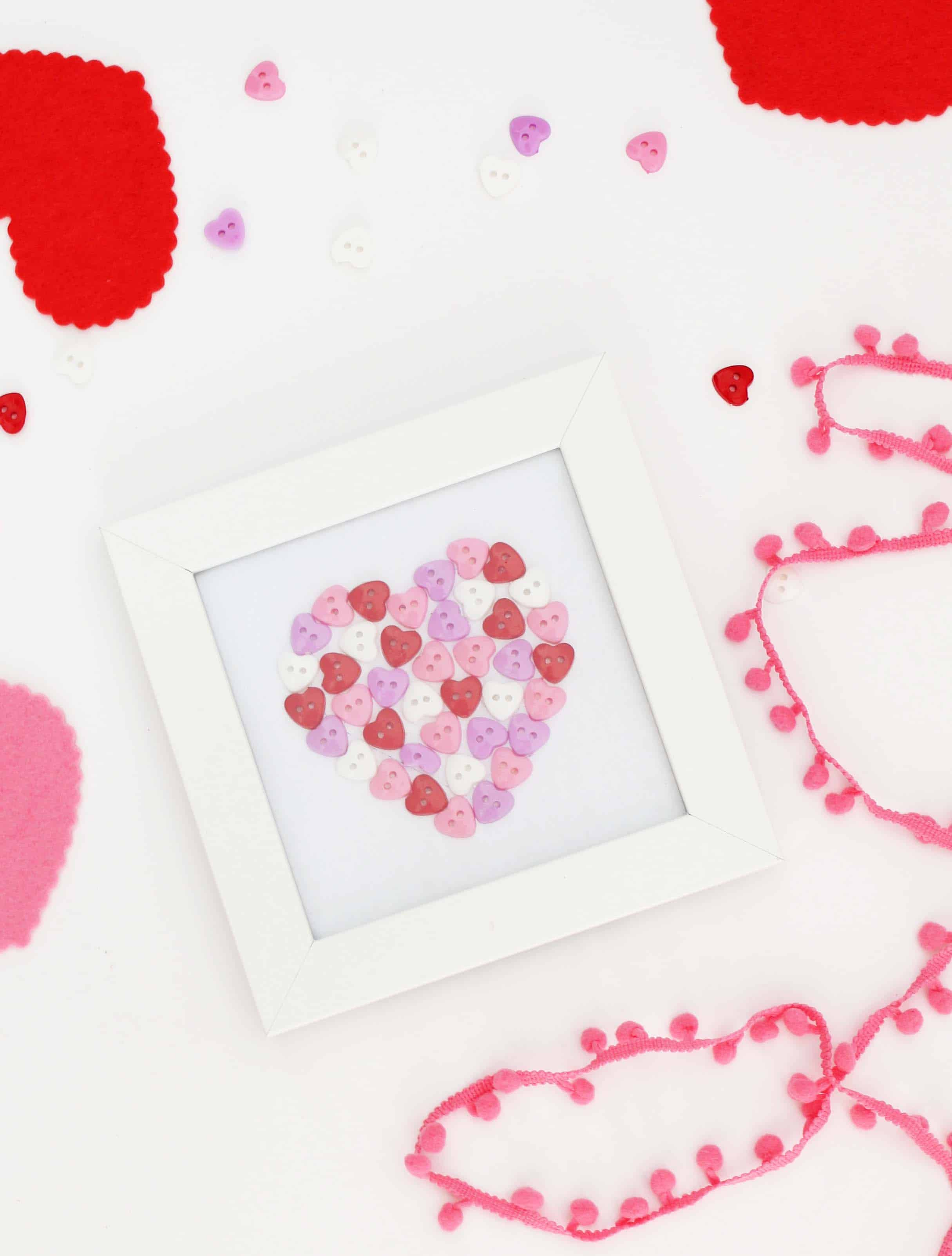 heart art made out of buttons in white picture frame