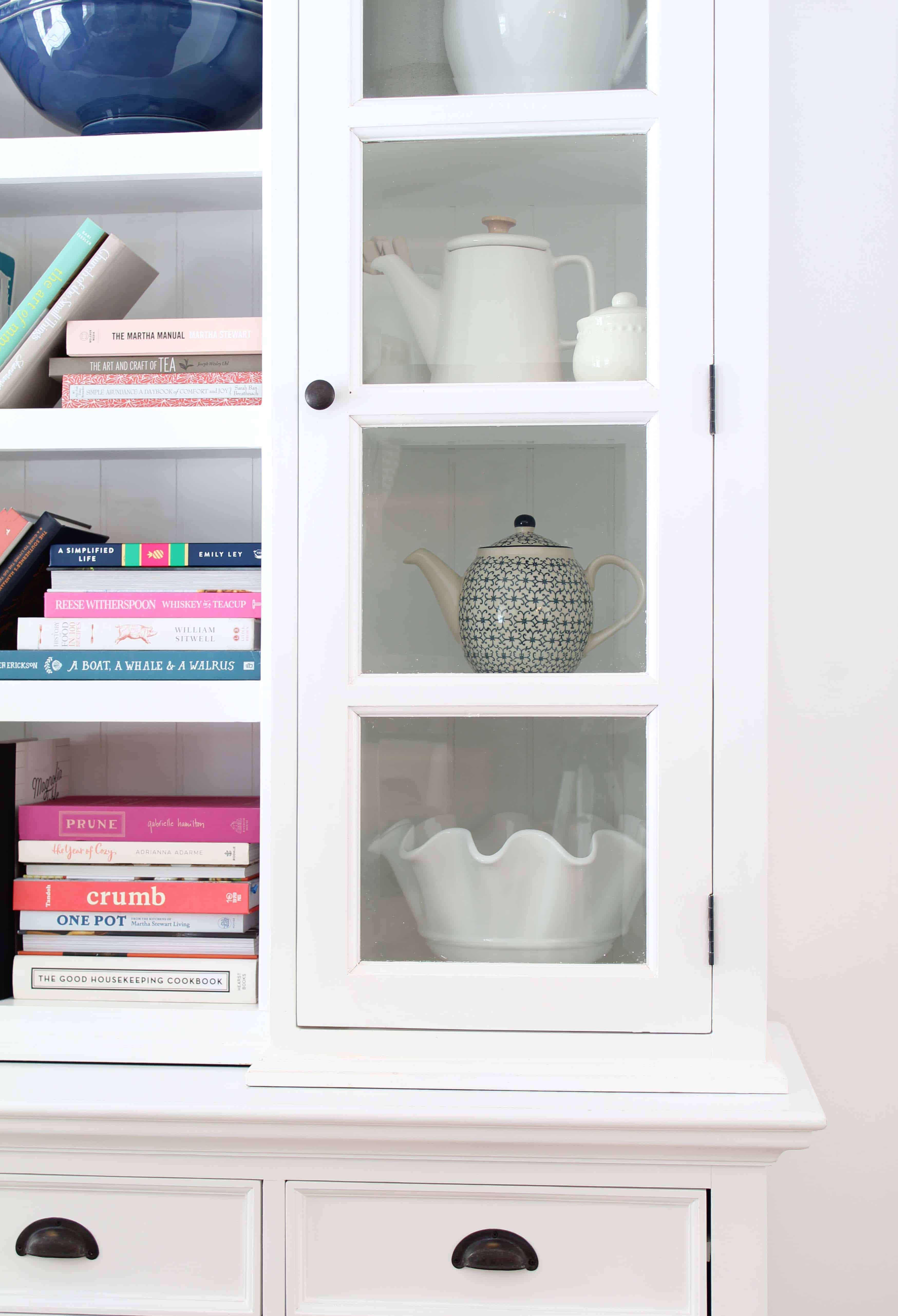 white library hutch with colorful books and teapots