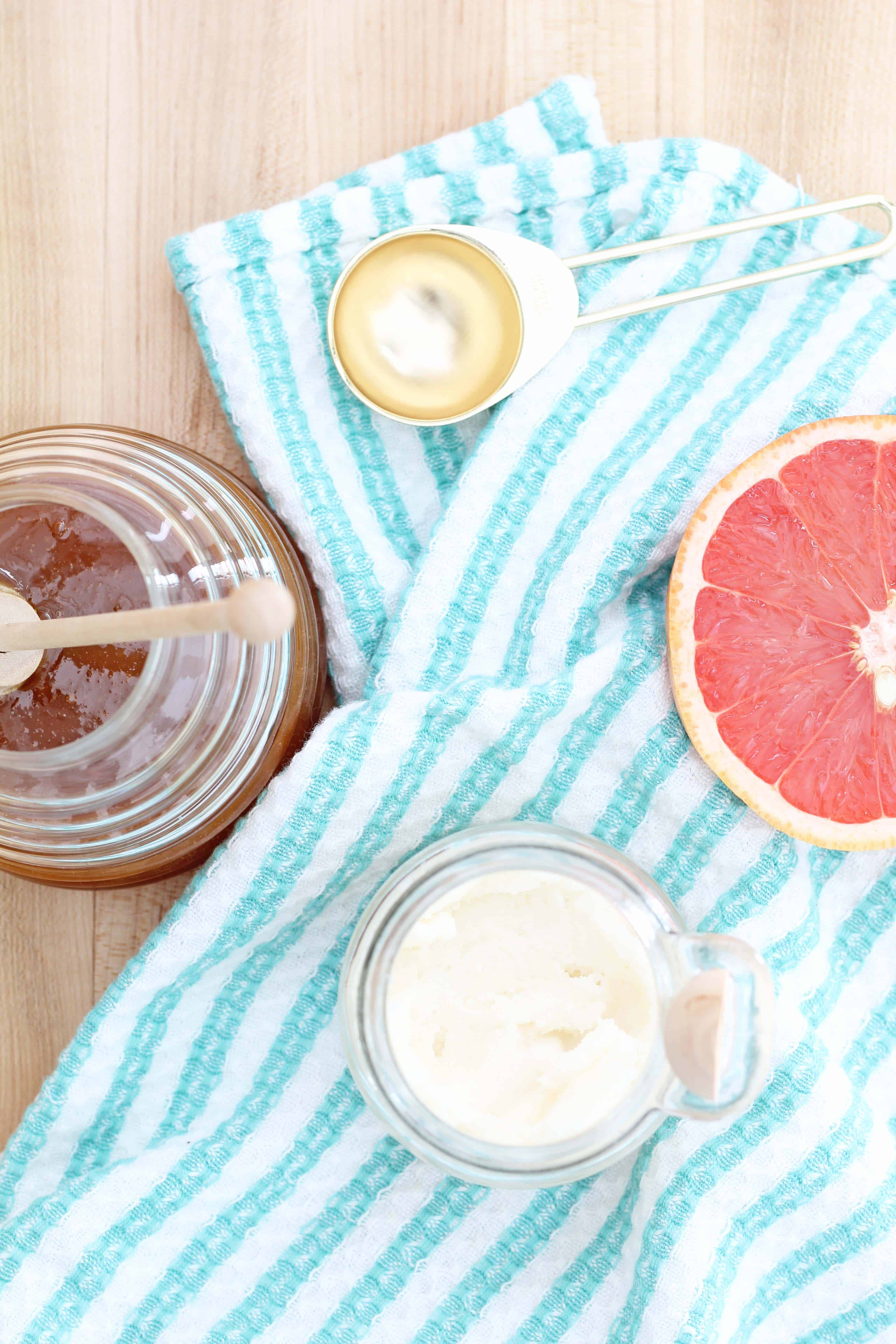 grapefruit, honey is glass beehive jar, gold measuring spoon, and apothecary jar
