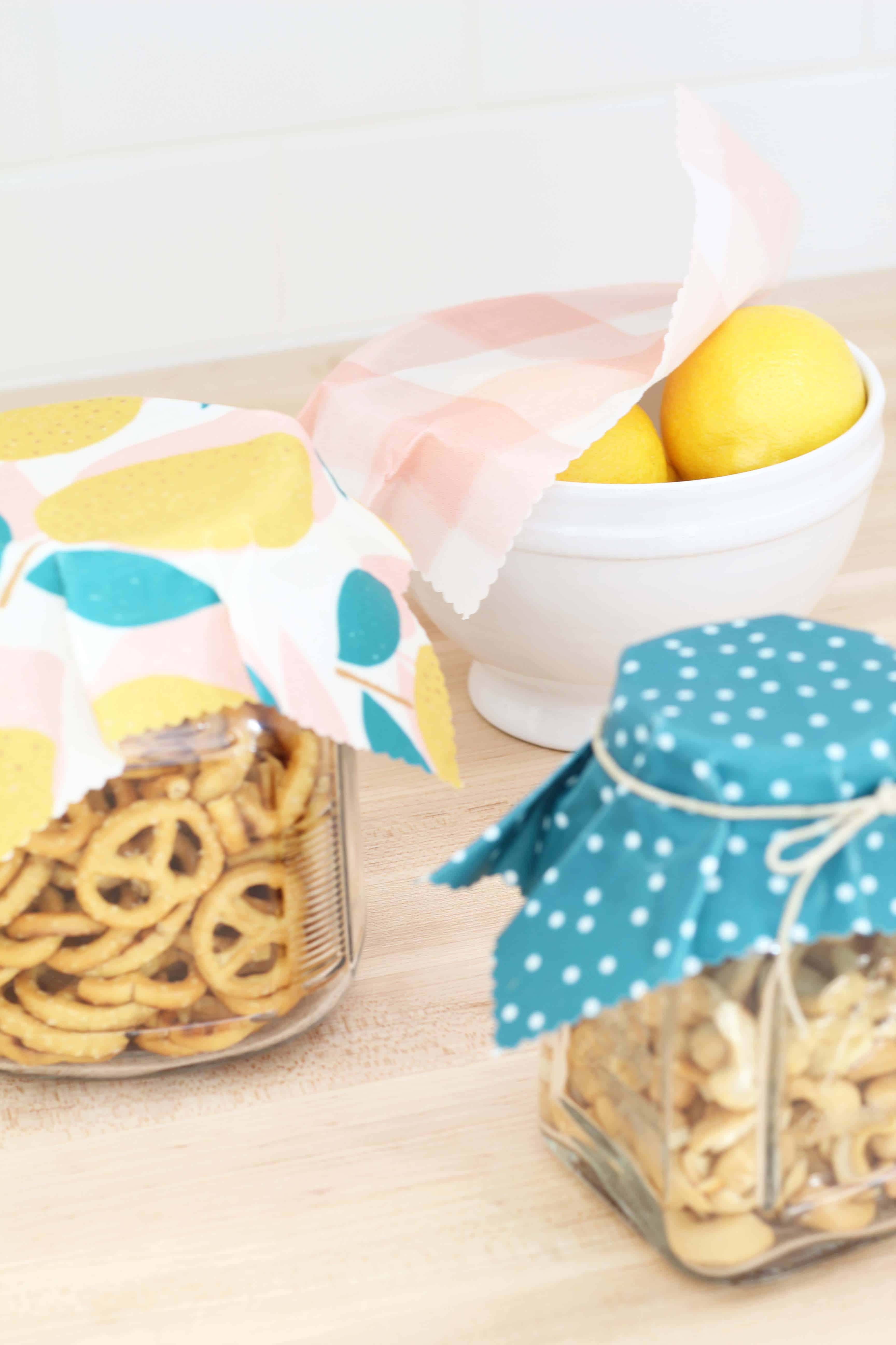 beeswax wrap in lemon print covering glass jars of food