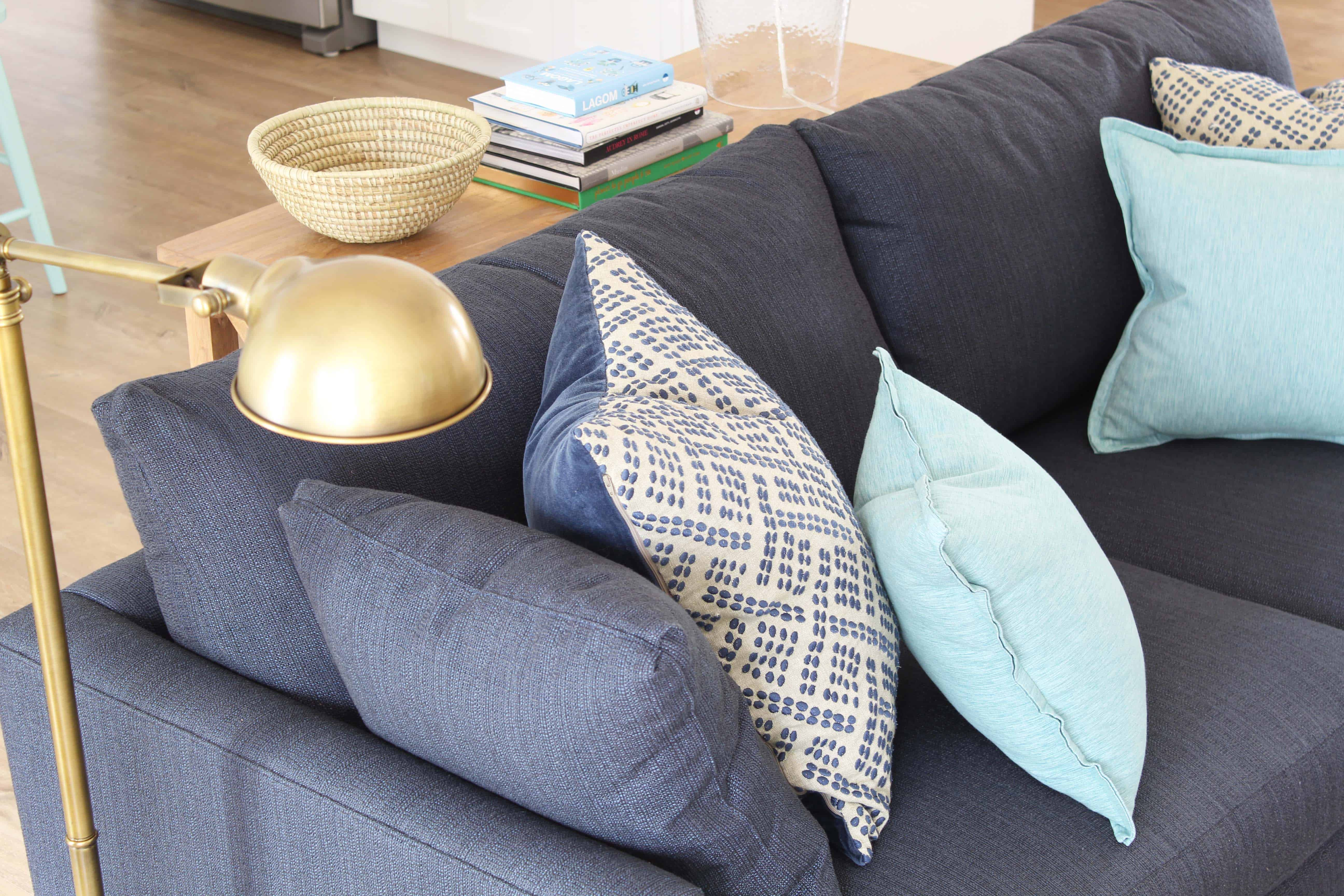 navy blue crate and barrel lounge II petite sofa, brass apothecary lamp, aqua throw pillows, and african woven basket