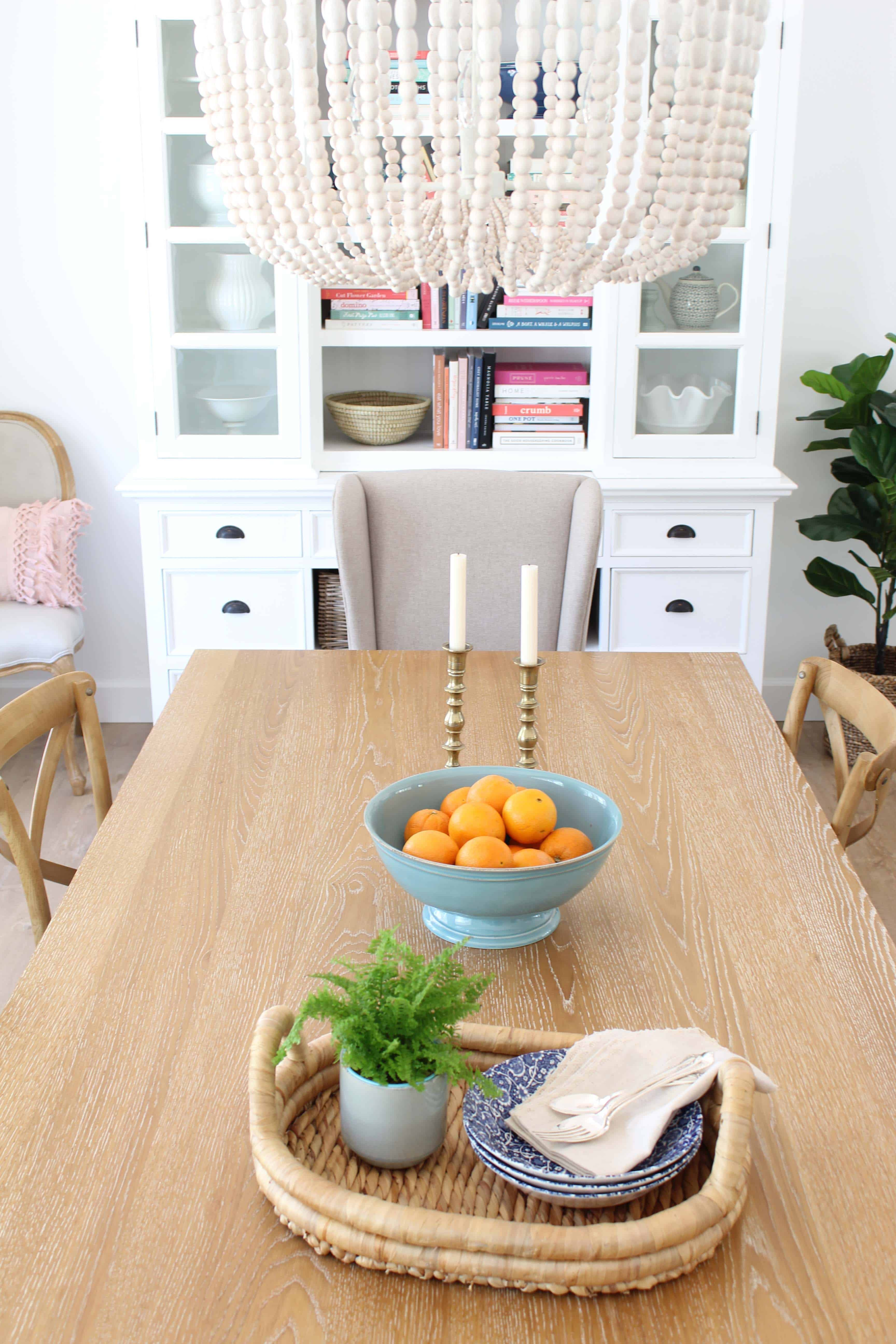 pier 1 dining room table, farmhouse bistro chairs, world market beaded chandelier, brass candlesticks, pottery barn aqua bowl with oranges