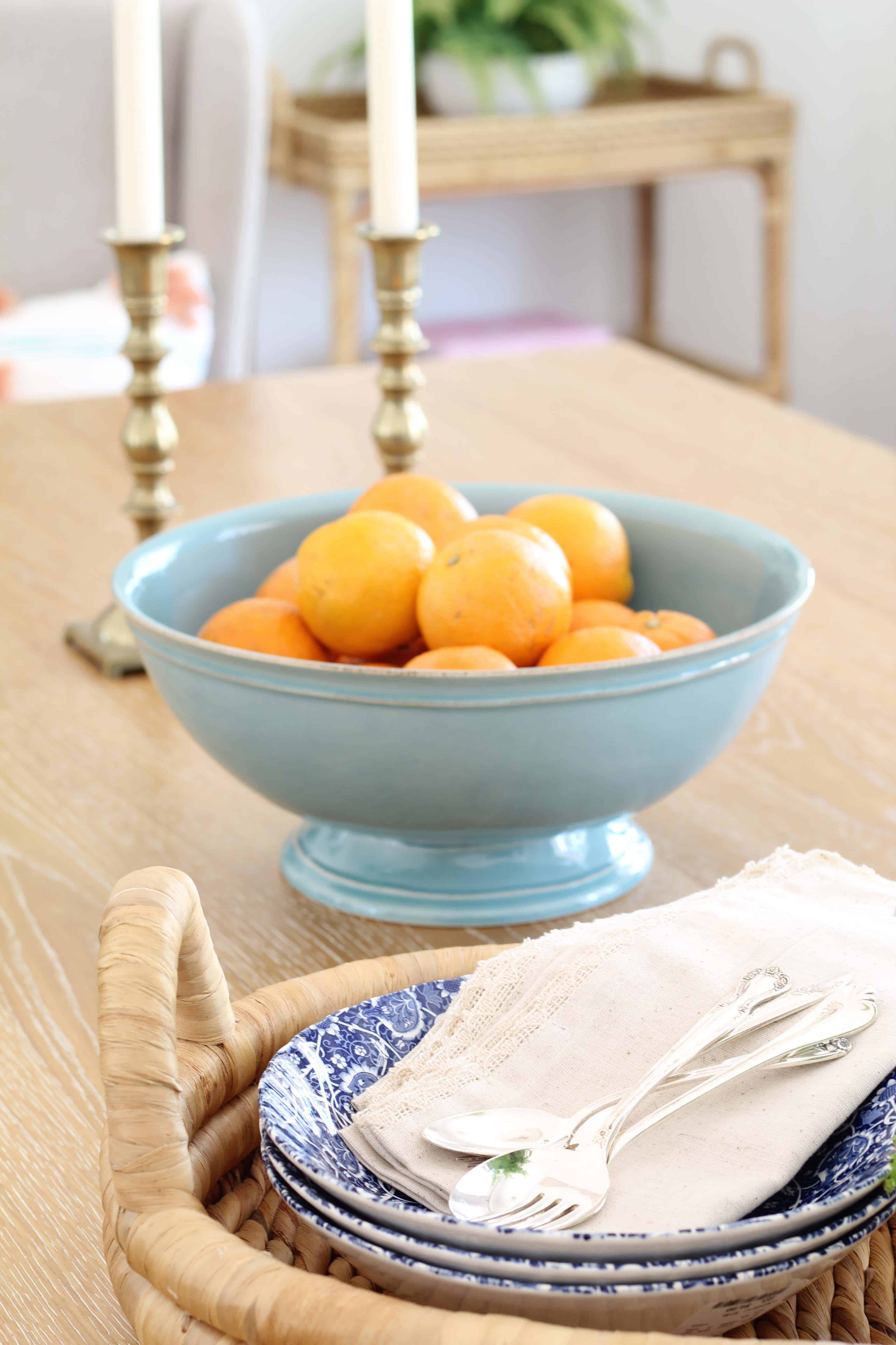 oranges in aqua bowl, brass candlesticks, blue transfer ware bowls with antique silverware