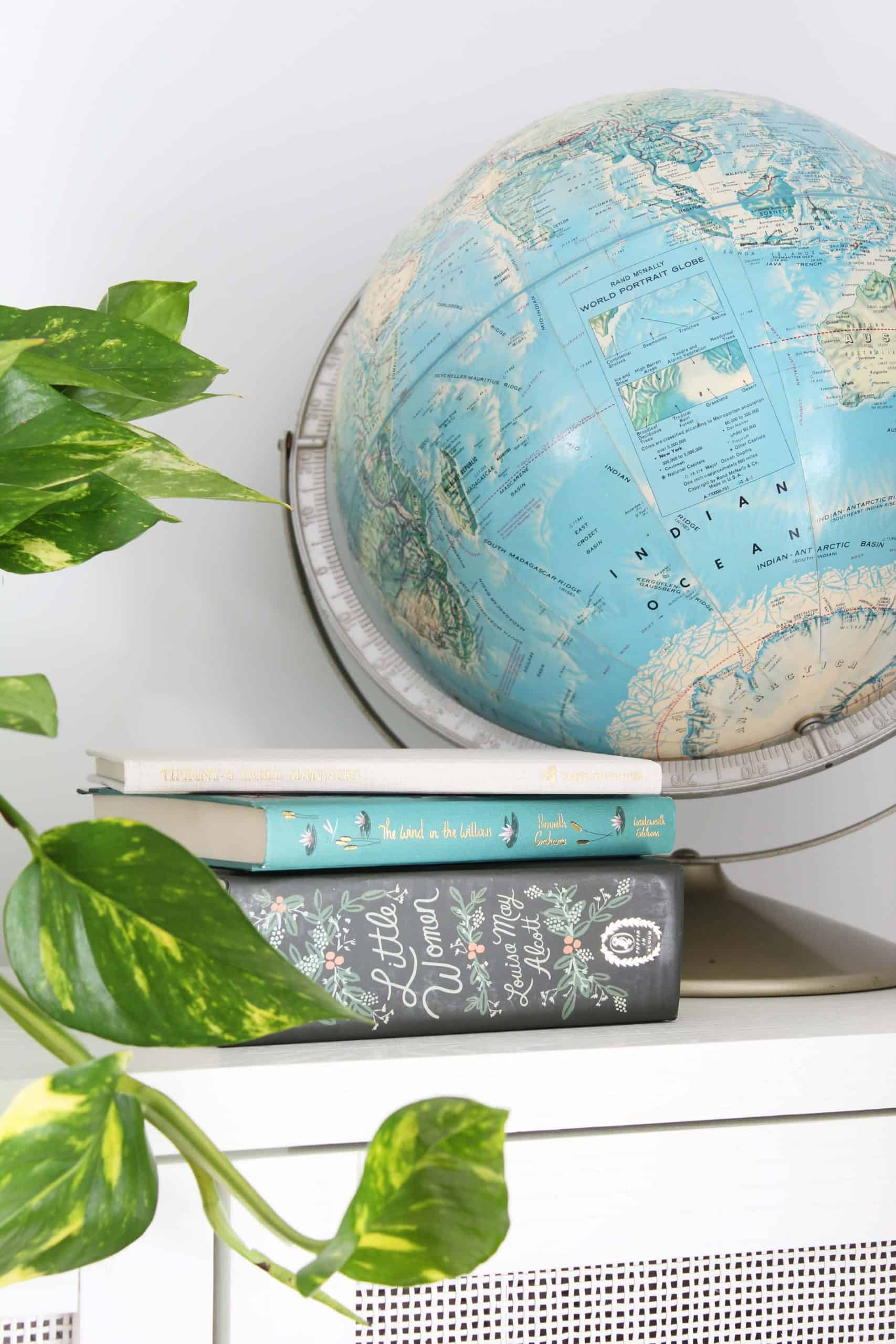 vintage globe, rifle paper co little women book, pothos plant