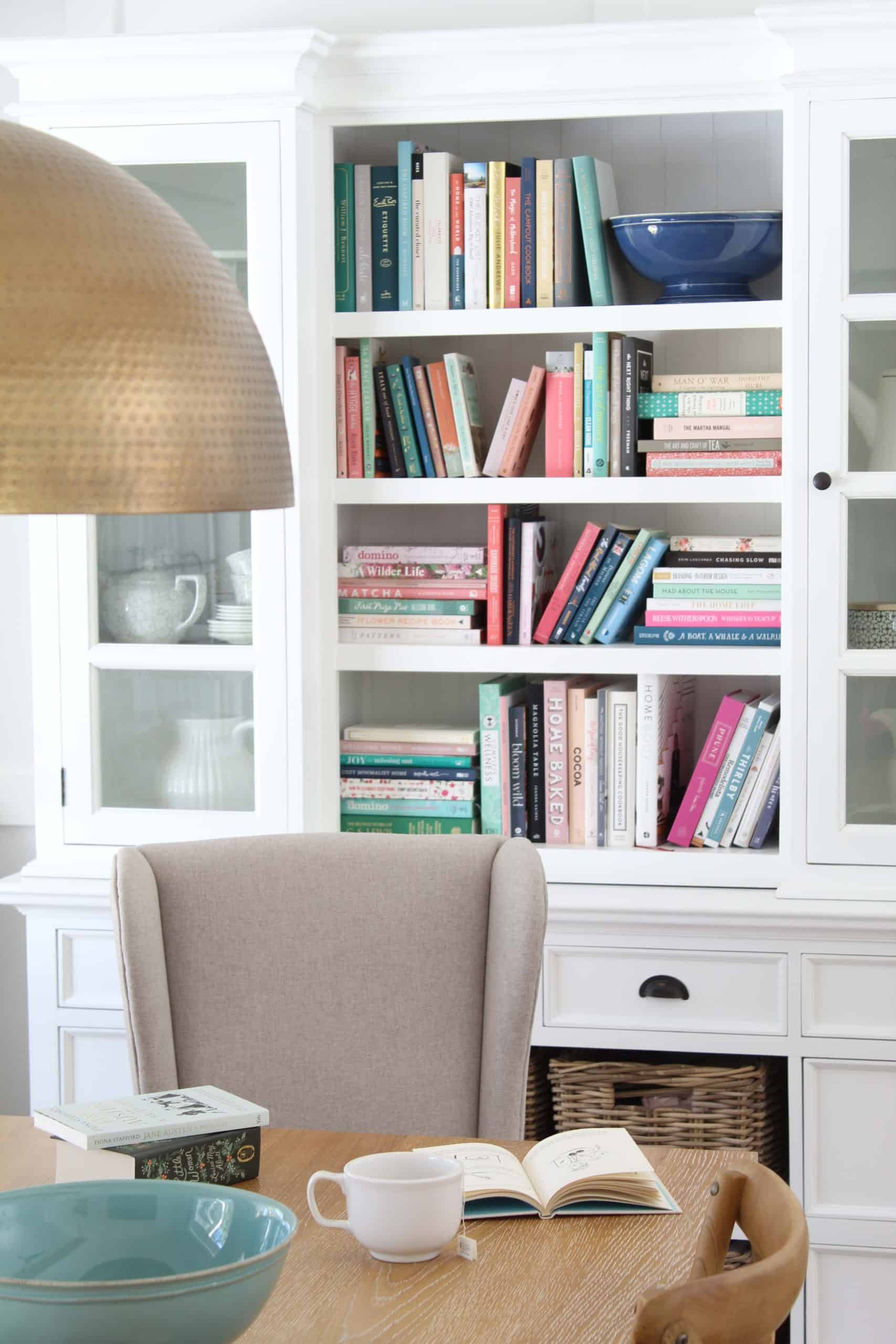 colorful books on bookshelf, brass dining pendant light, large white book case hutch
