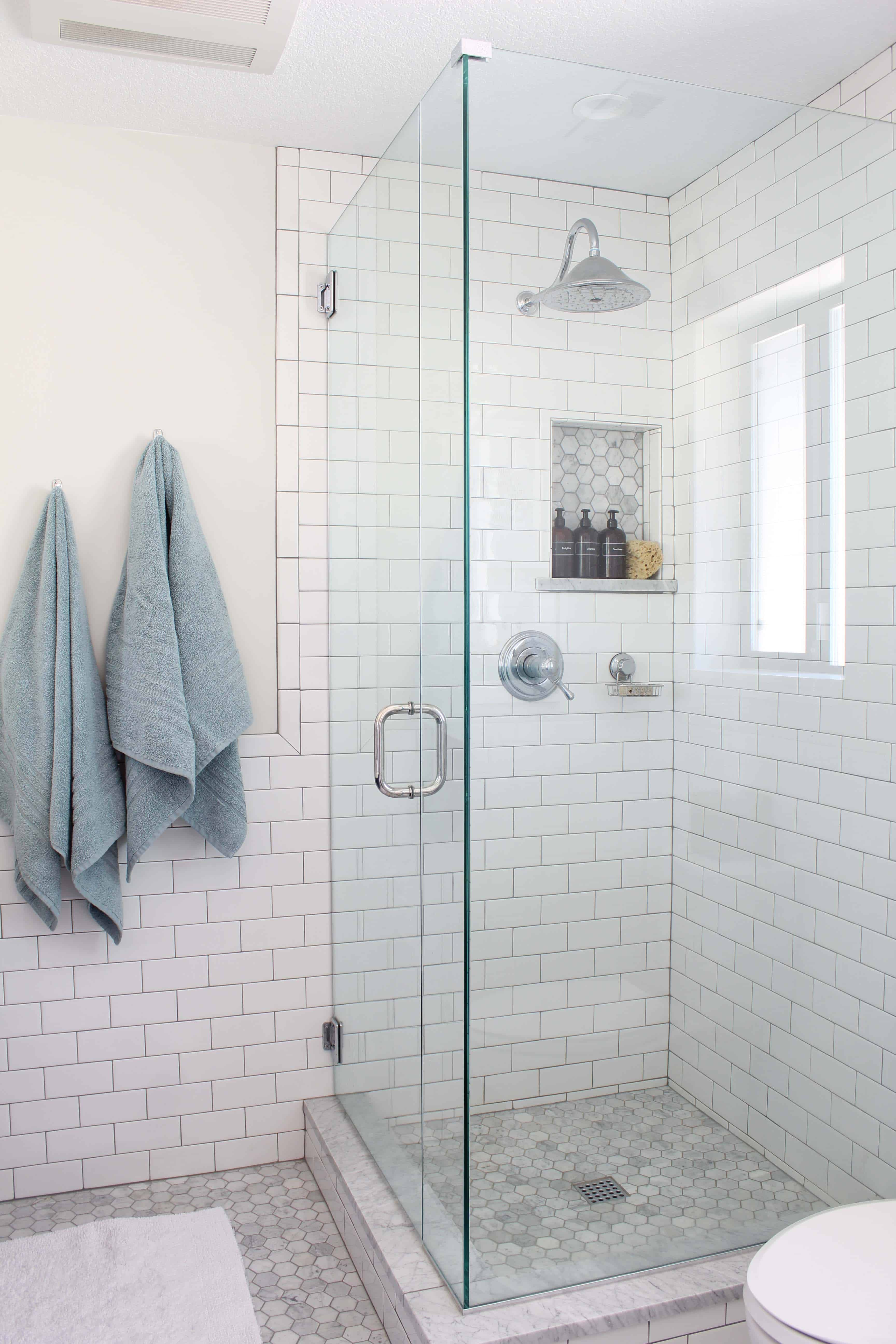 white subway tile and marble hex tile shower
