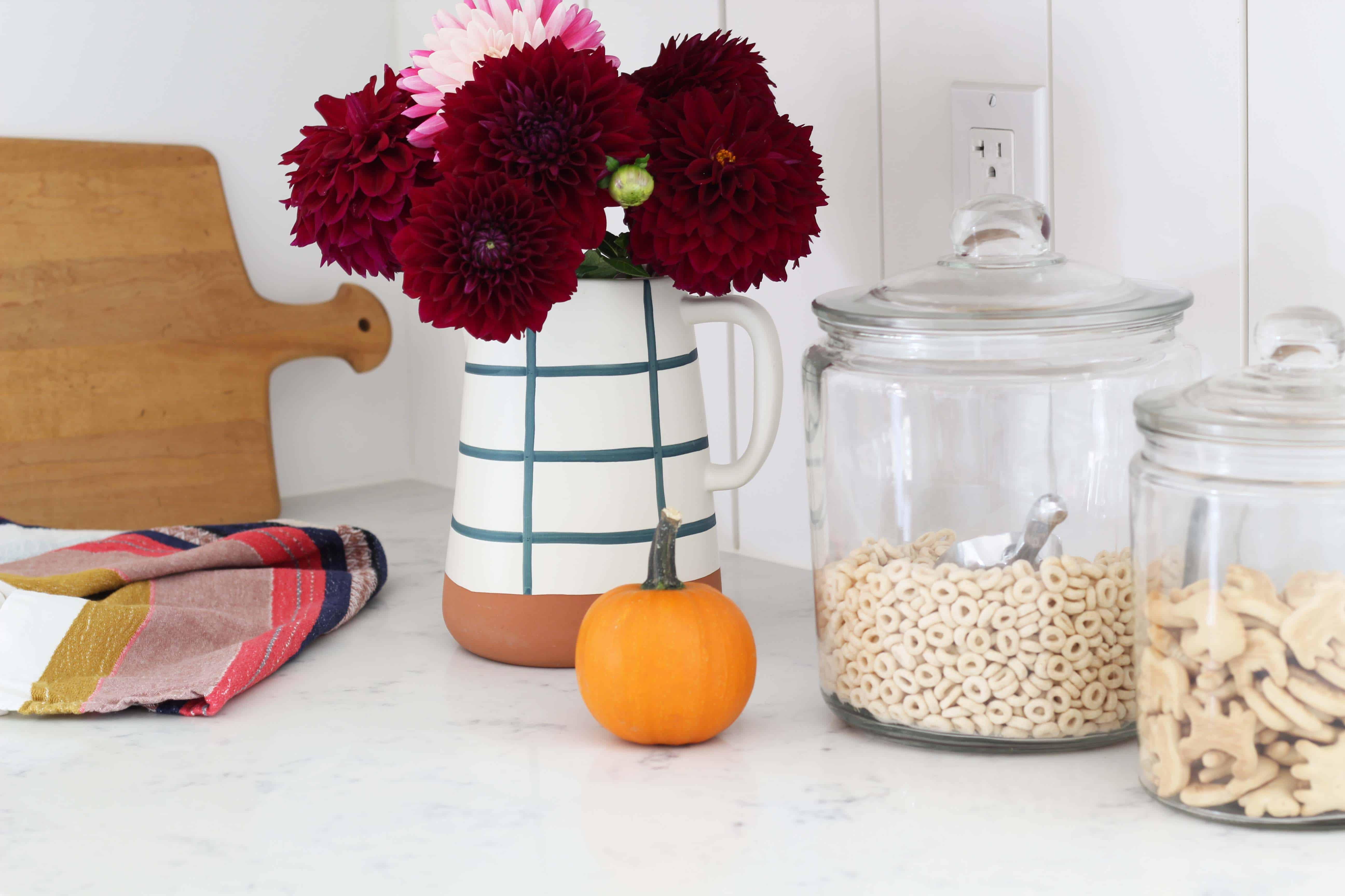 fall mums in threshold magnolia home pitcher, mini pumpkin decor, cheerios in glass canister