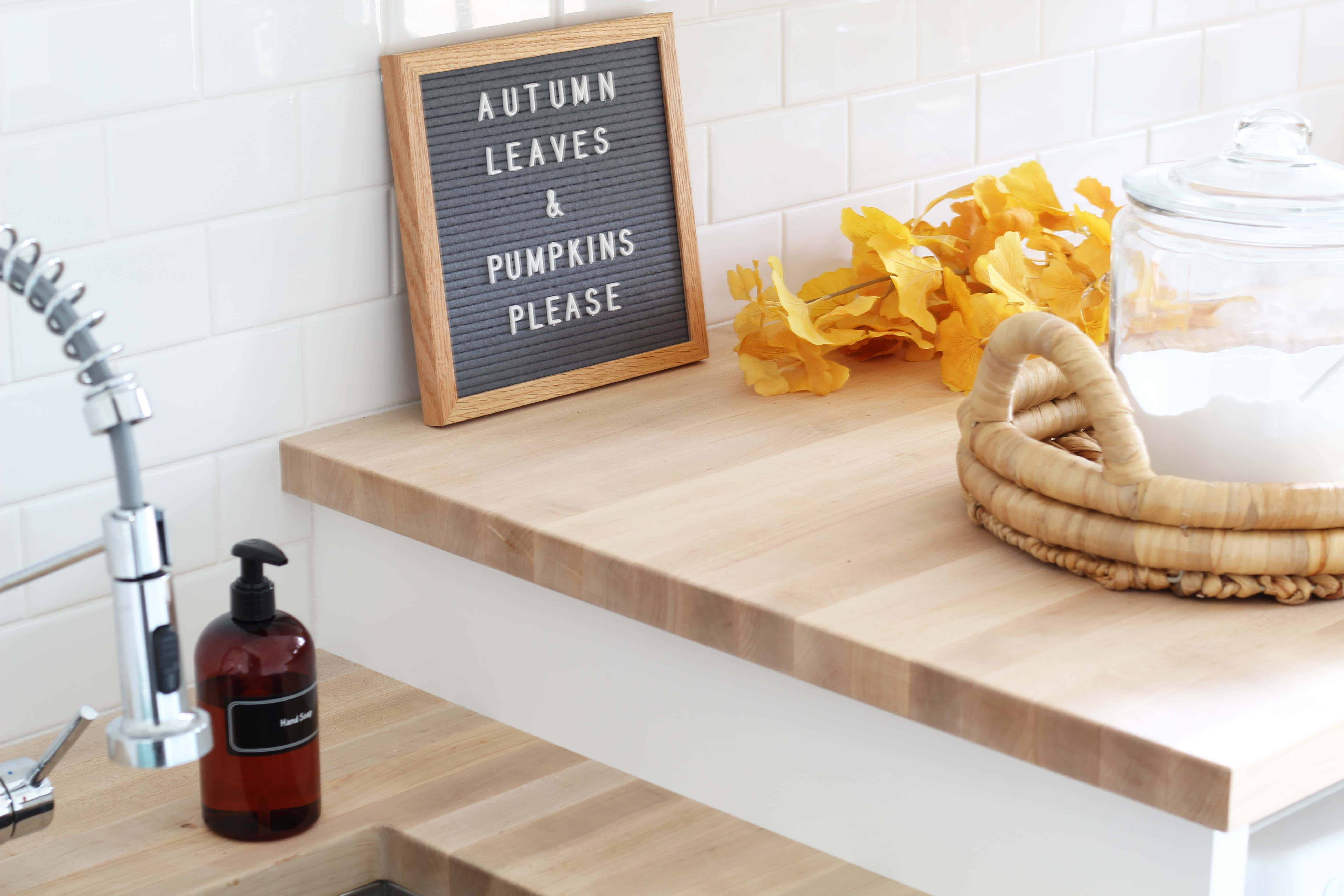 letterfold letterboard, amber soap dispenser bottle, fall gingko leaves, laundry room with butcher block counters