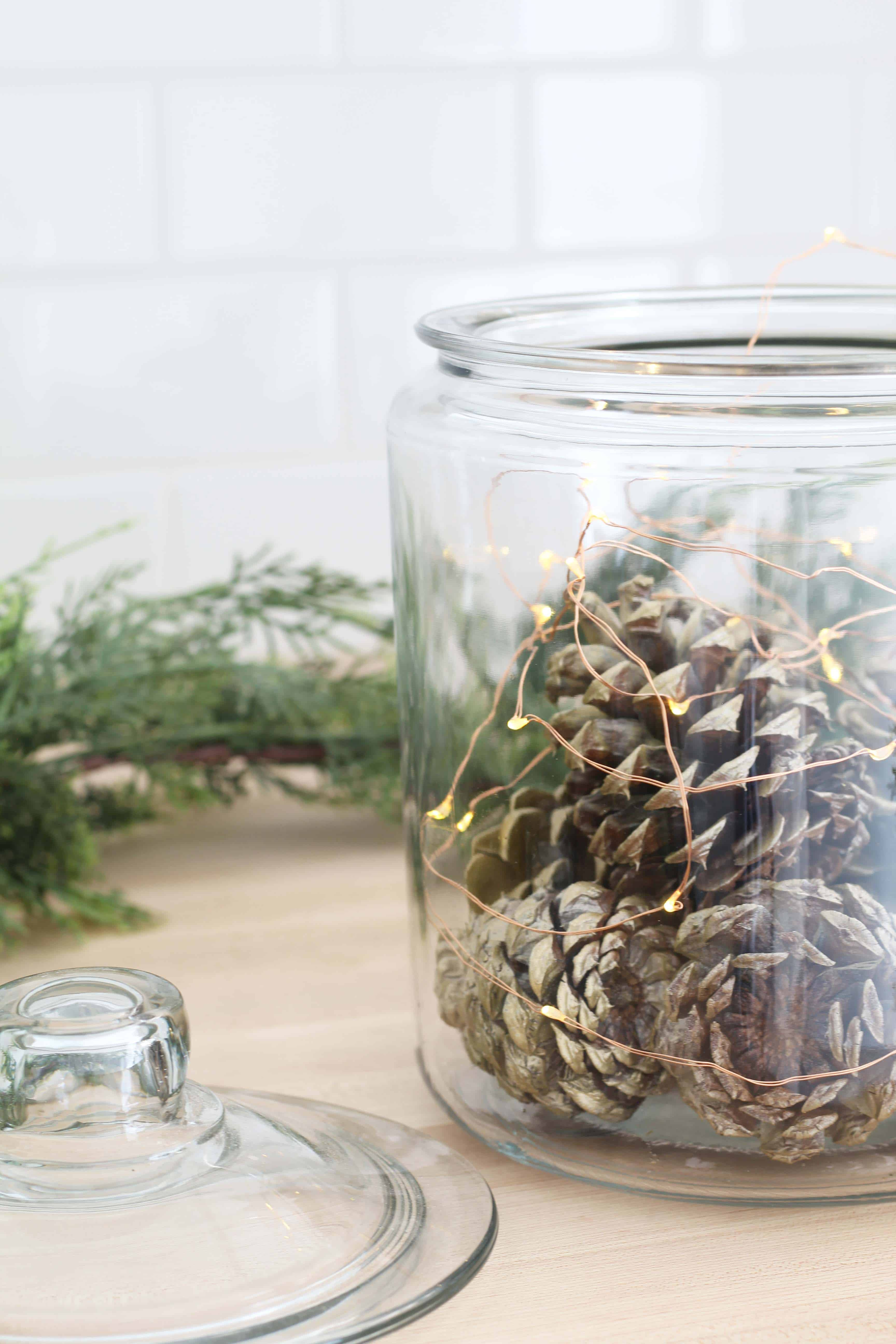 pinecones in glass canister with fairy lights
