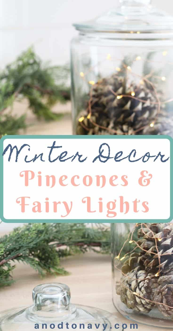 gold pinecones in glass canister with fairy lights