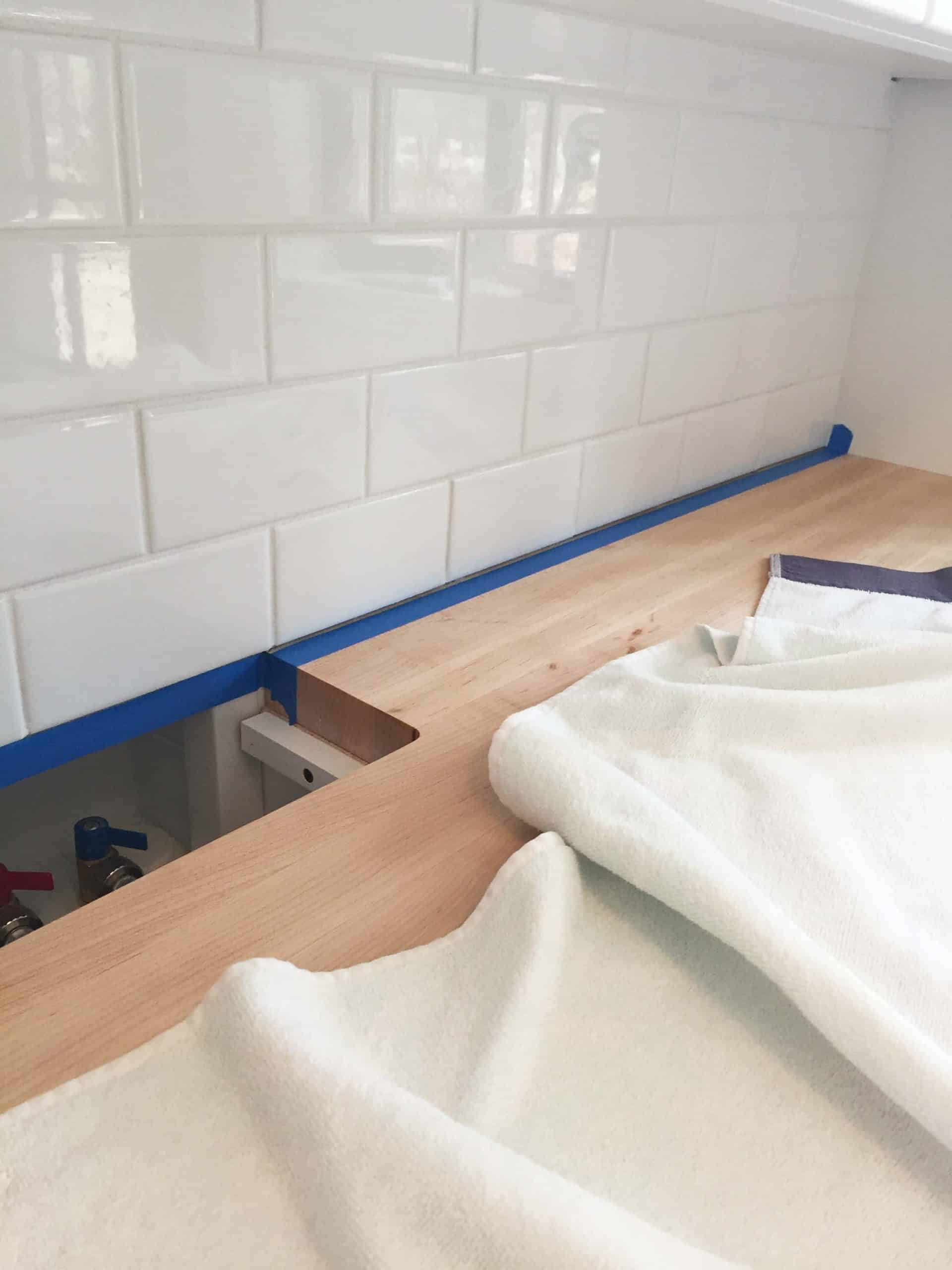 white subway tile backsplash in laundry room with butcher block countertops