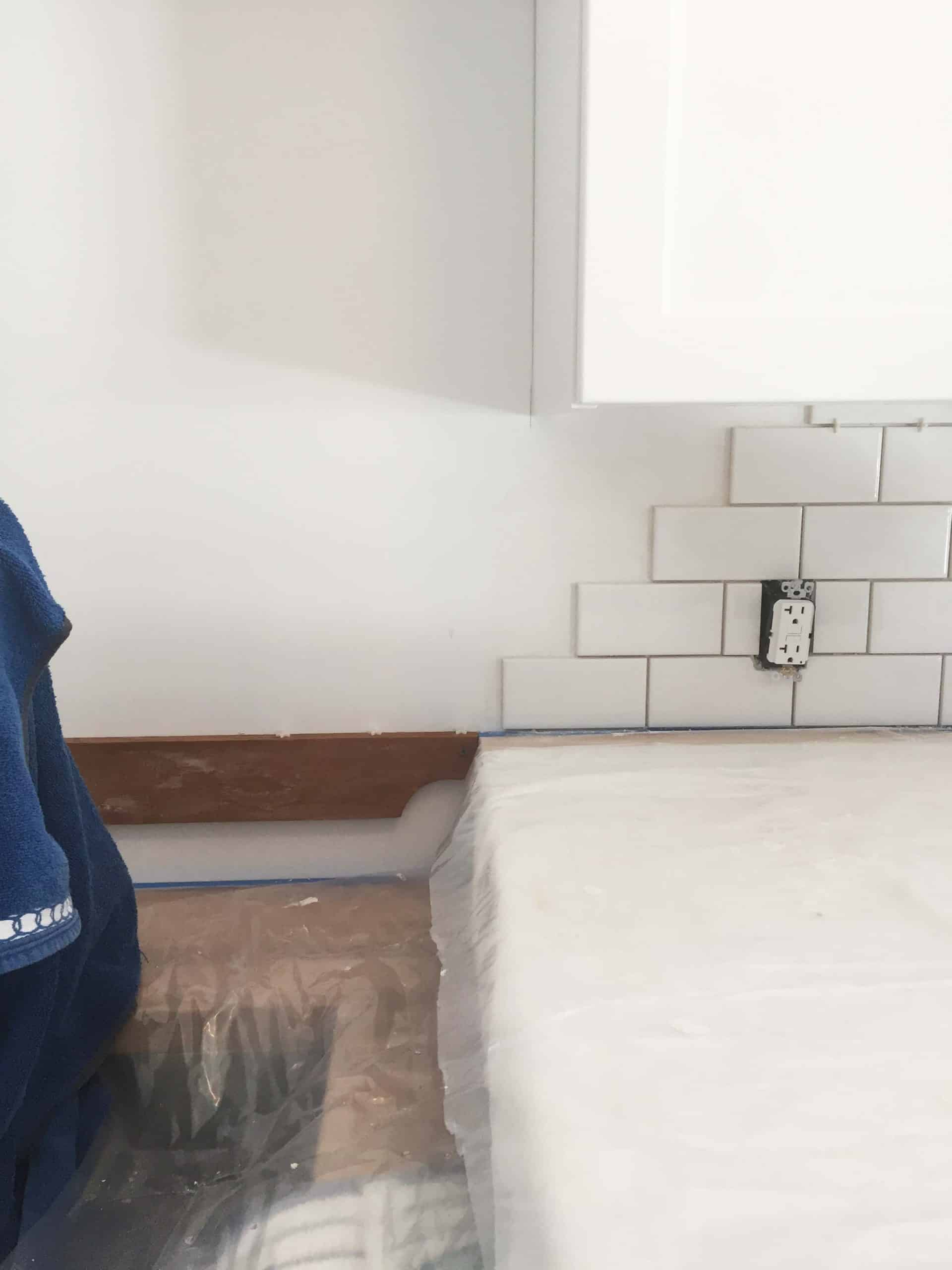 two different countertop heights in laundry room with subway tile backsplash