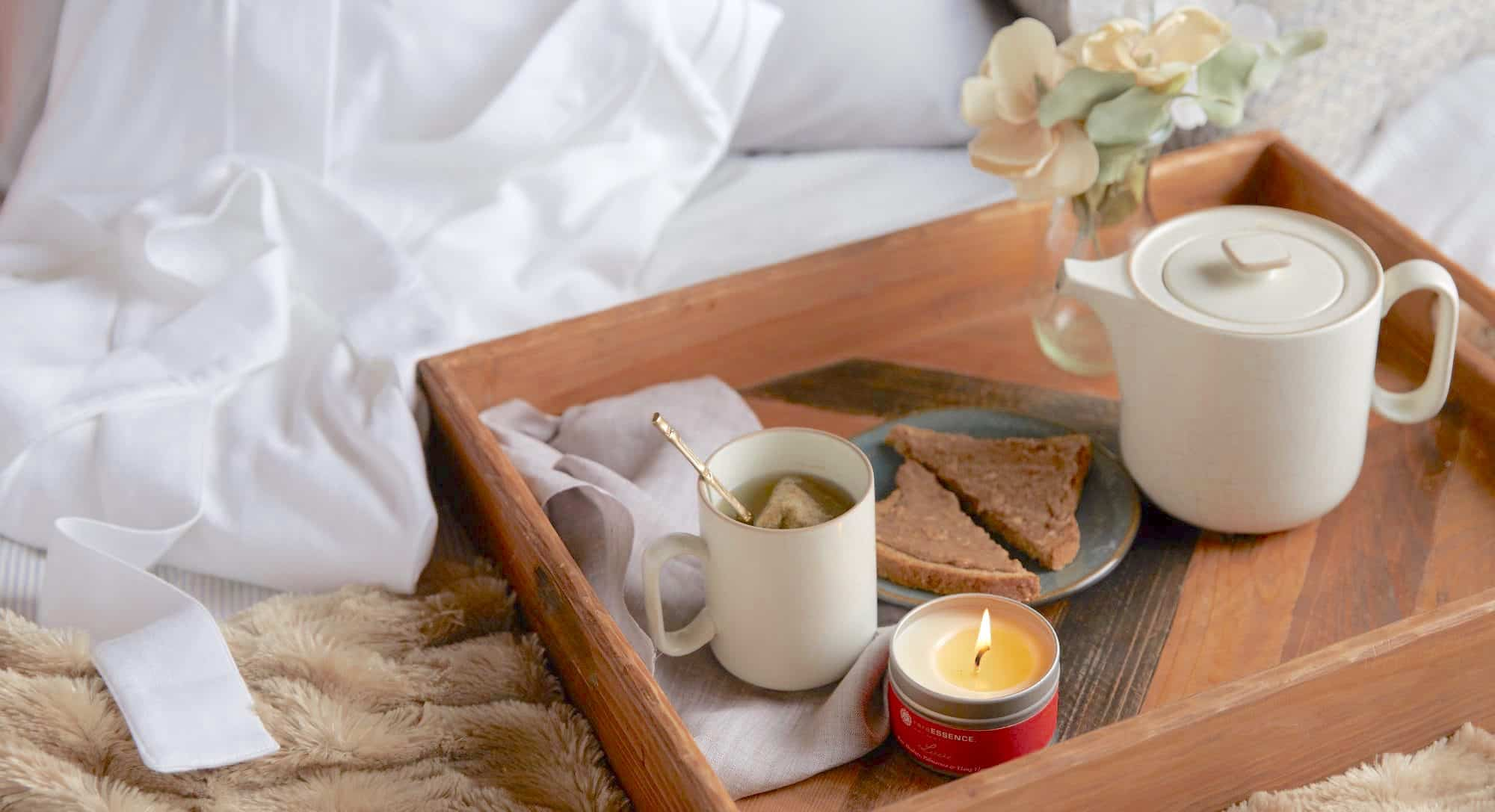 wood tray with tea and toast and candle, breakfast in bed, hygge style,