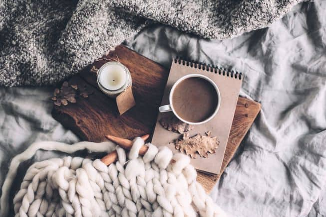 chunky knit blanket, hot chocolate and candle in bed, cozy hygge candle, winter candle with tea