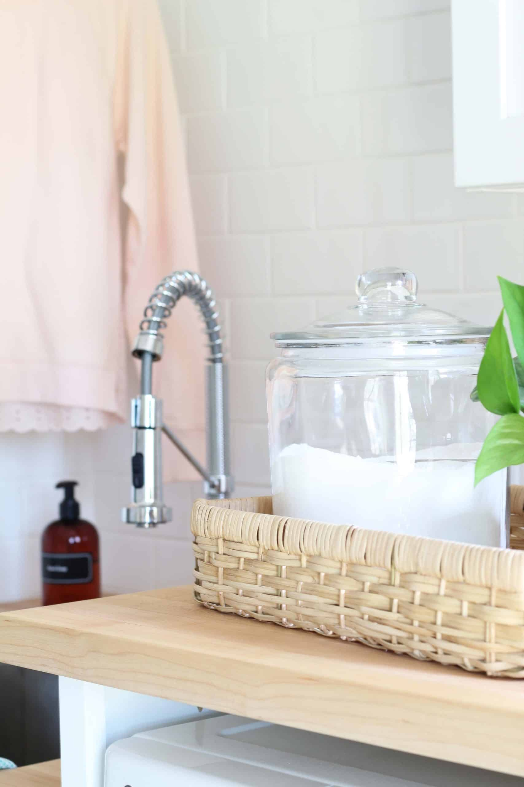 glass canister with laundry soap, maple butcher block countertops, white subway tile backsplash in laundry room, farmhouse style laundry room makeover
