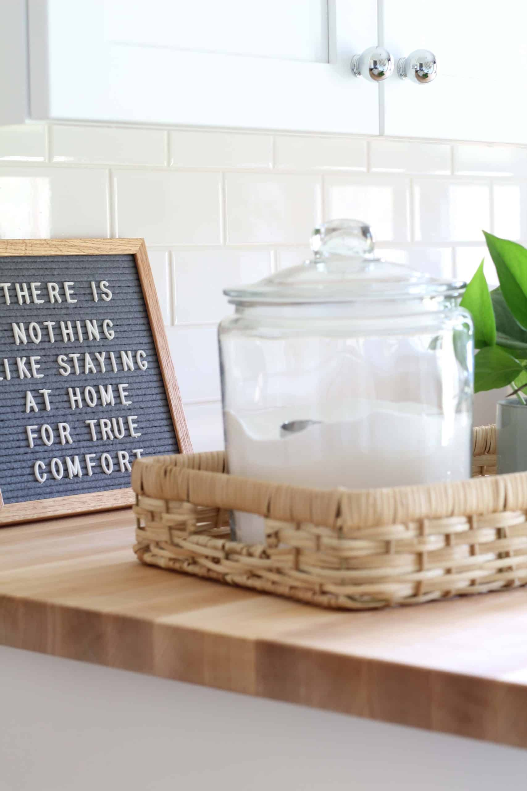 gray felt letter board, glass canister with laundry soap, maple butcher block countertops