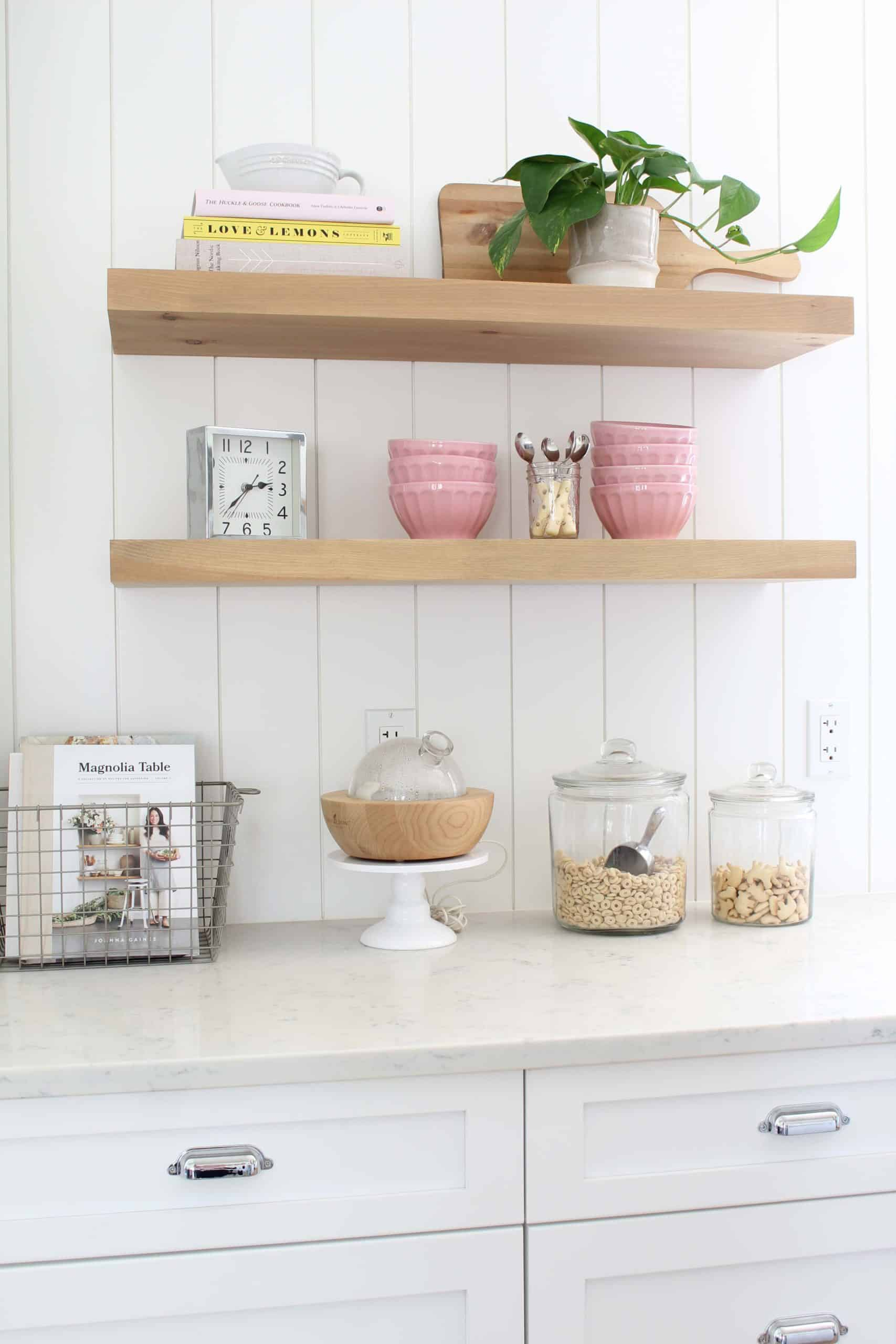 light wood open kitchen shelving, pink anthropologie bowls