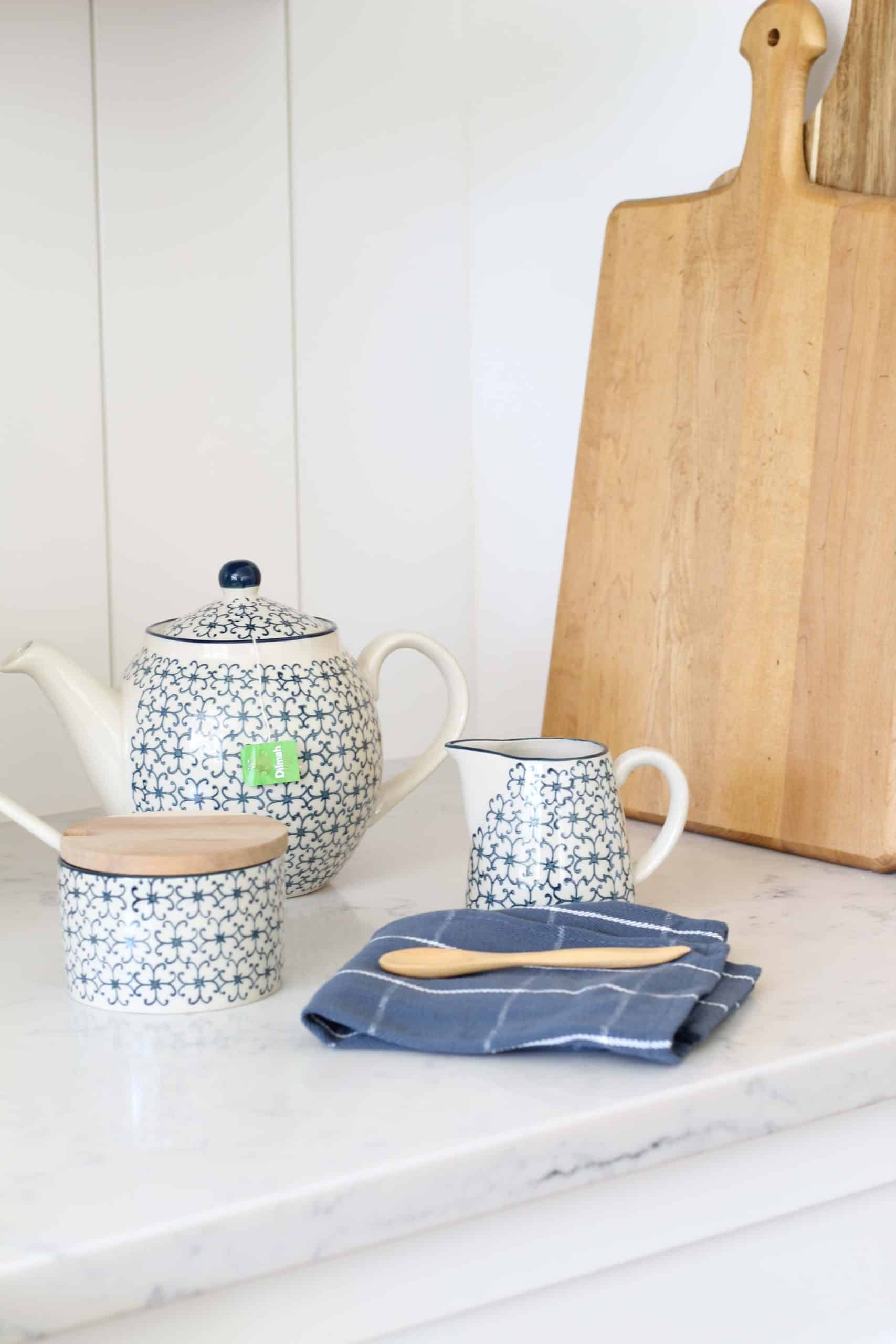 blue and white teapot, blue and white sugar bowl, blue and white creamer, natural wood breadboard, vertical shiplap kitchen backsplash, magnolia home wood spoons