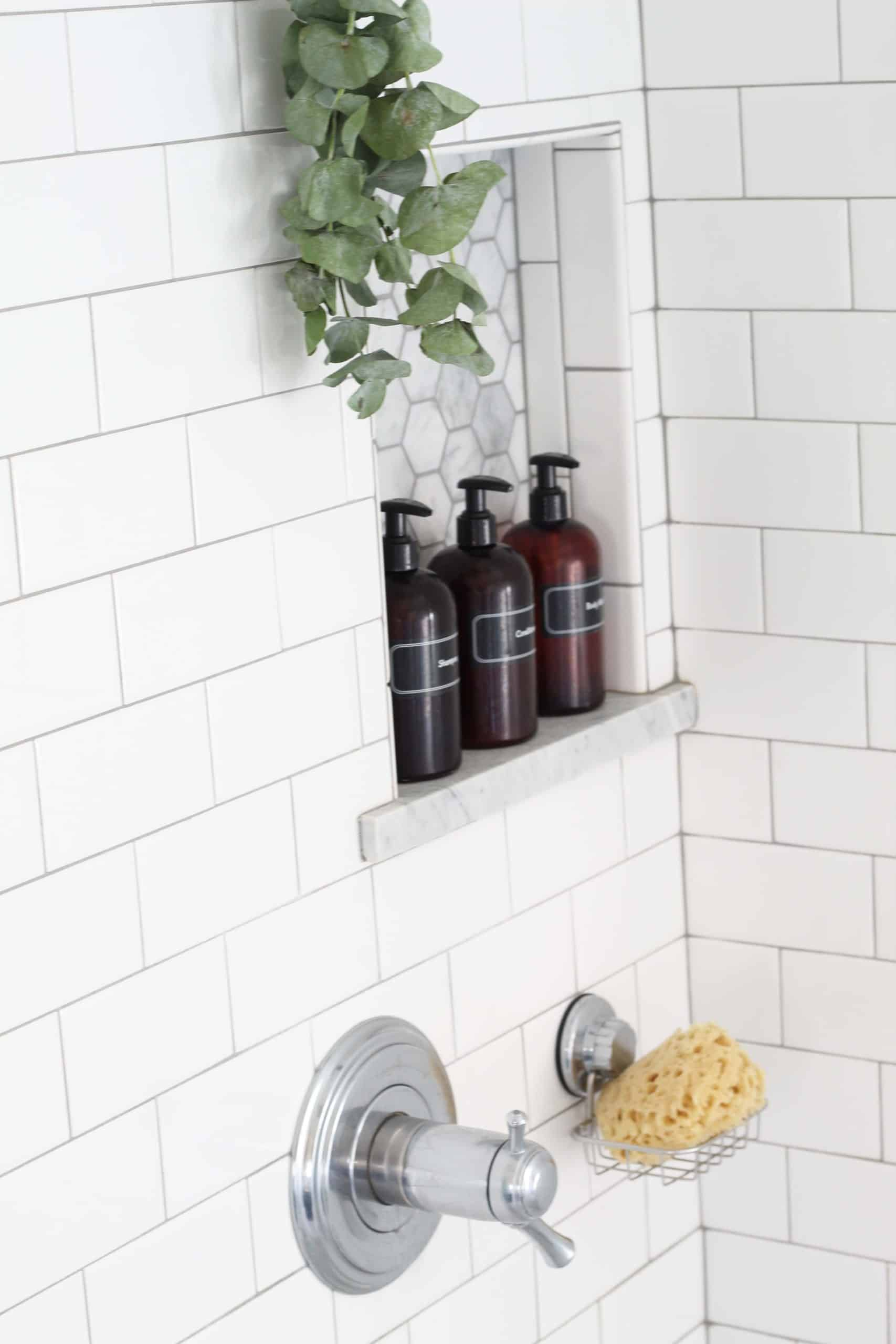 eucalyptus hanging in shower with amber pump shower bottles