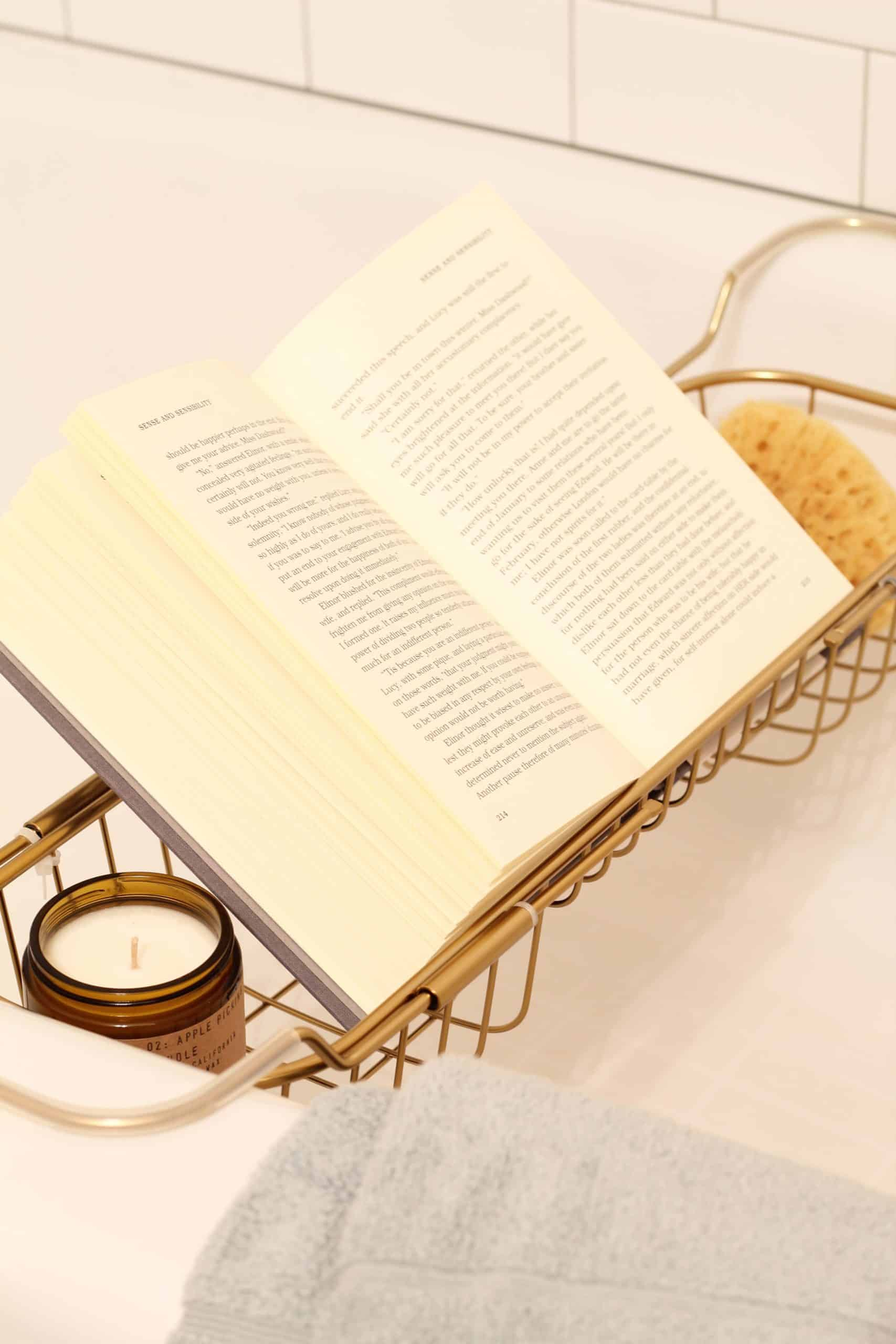 open book on expandable bathtub tray with candle and sea sponge