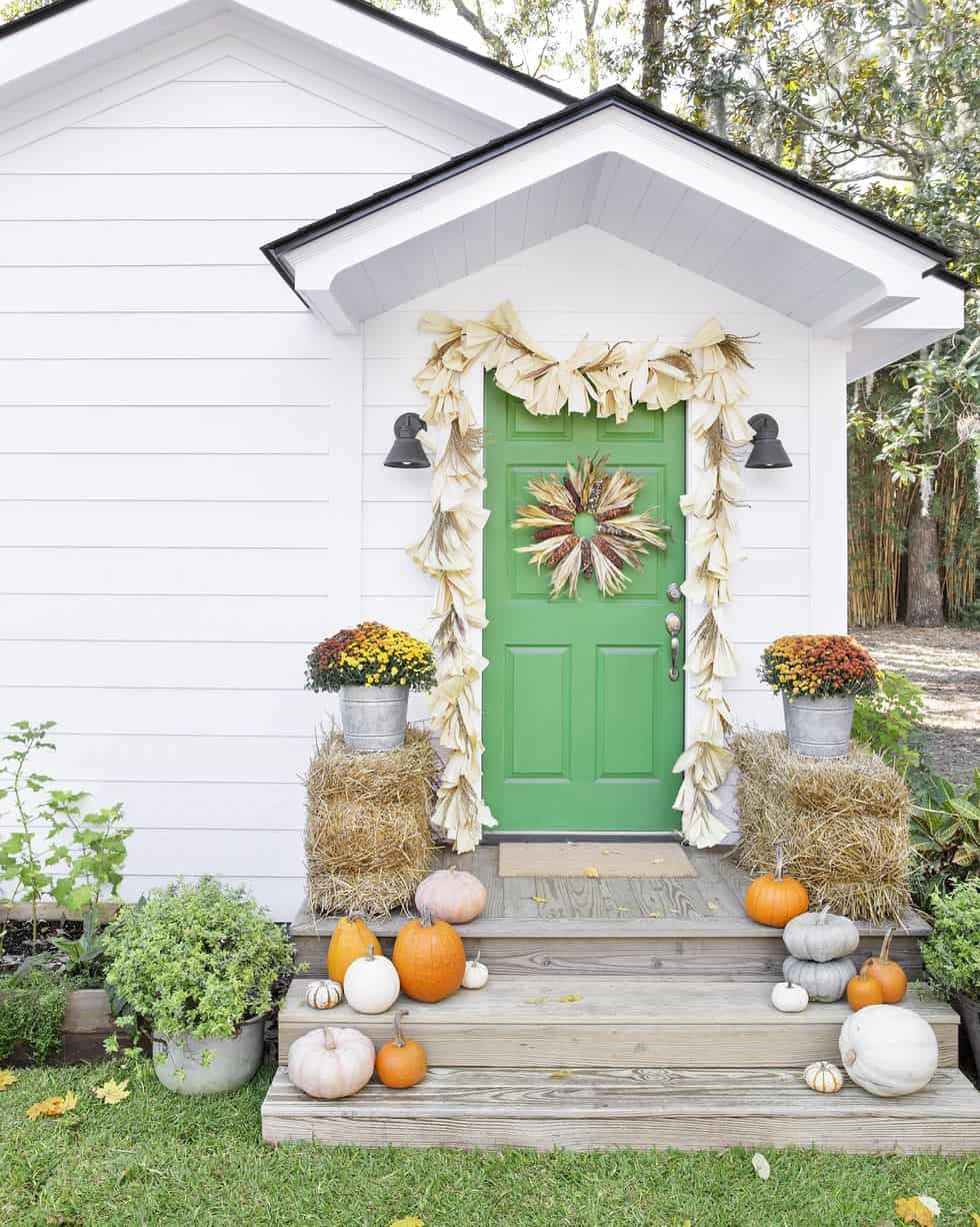 white cottage with green door and pumpkins, mums, and corn husk garland on front porch