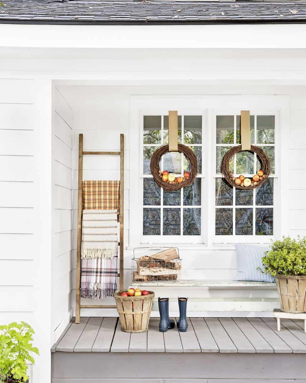 white farmhouse with blanket ladder on front porch and grapevine wreaths