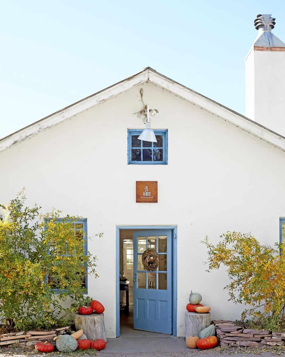 white cottage with blue door and pumpkins sitting on tree stumps