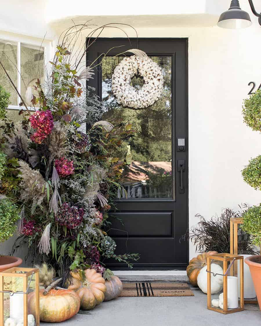 front porch with pumpkins, wood lanterns, and cotton wreath