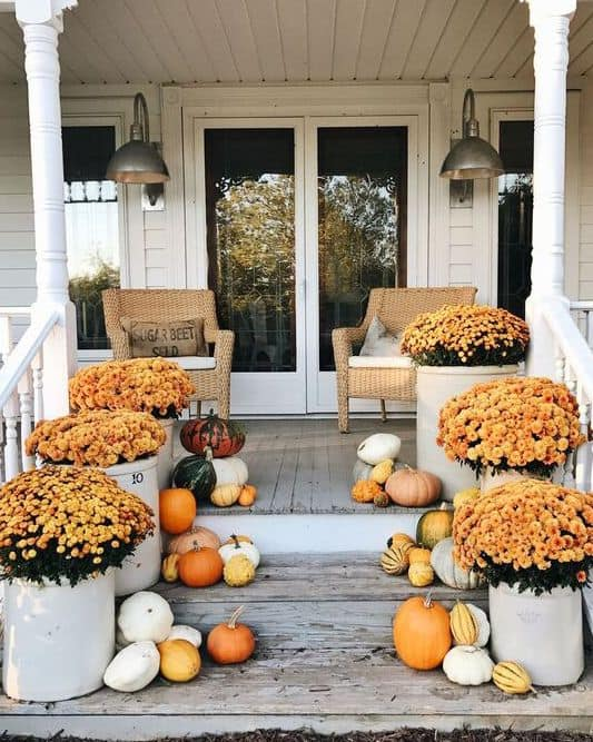 white farmhouse with oversized mums in crocks on front porch