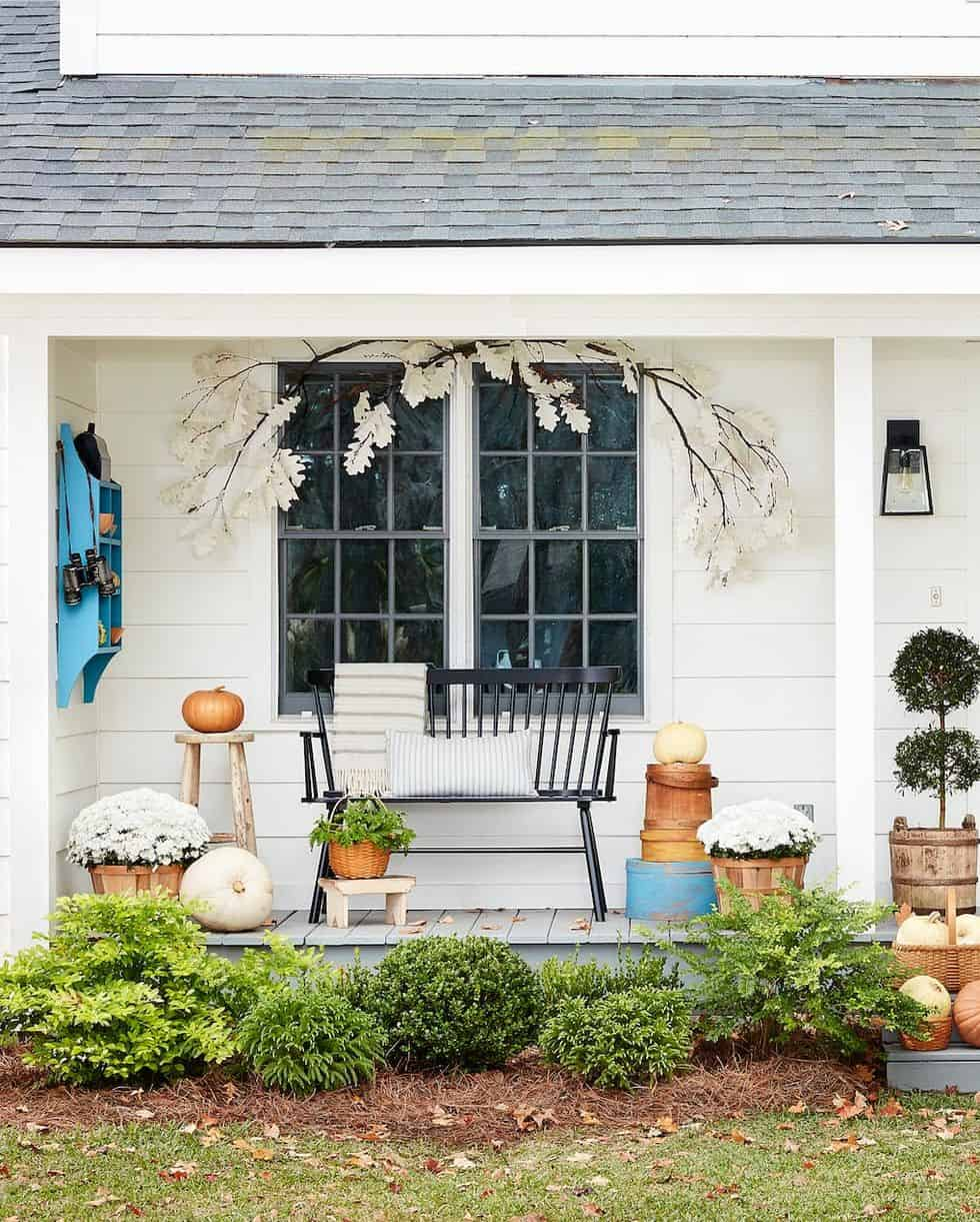 white farmhouse with pumpkins and mums on front porch