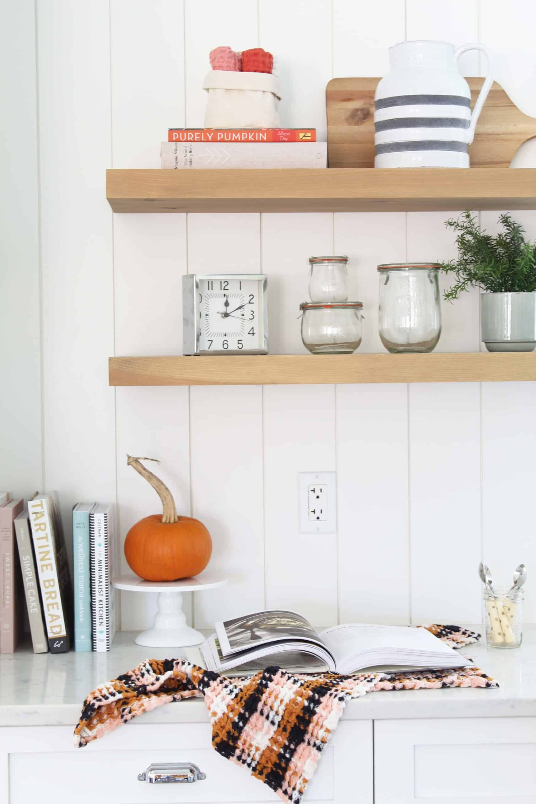 open kitchen shelving with wreck tulip jars, anthropologie dish cloths and striped pitcher, and pumpkin