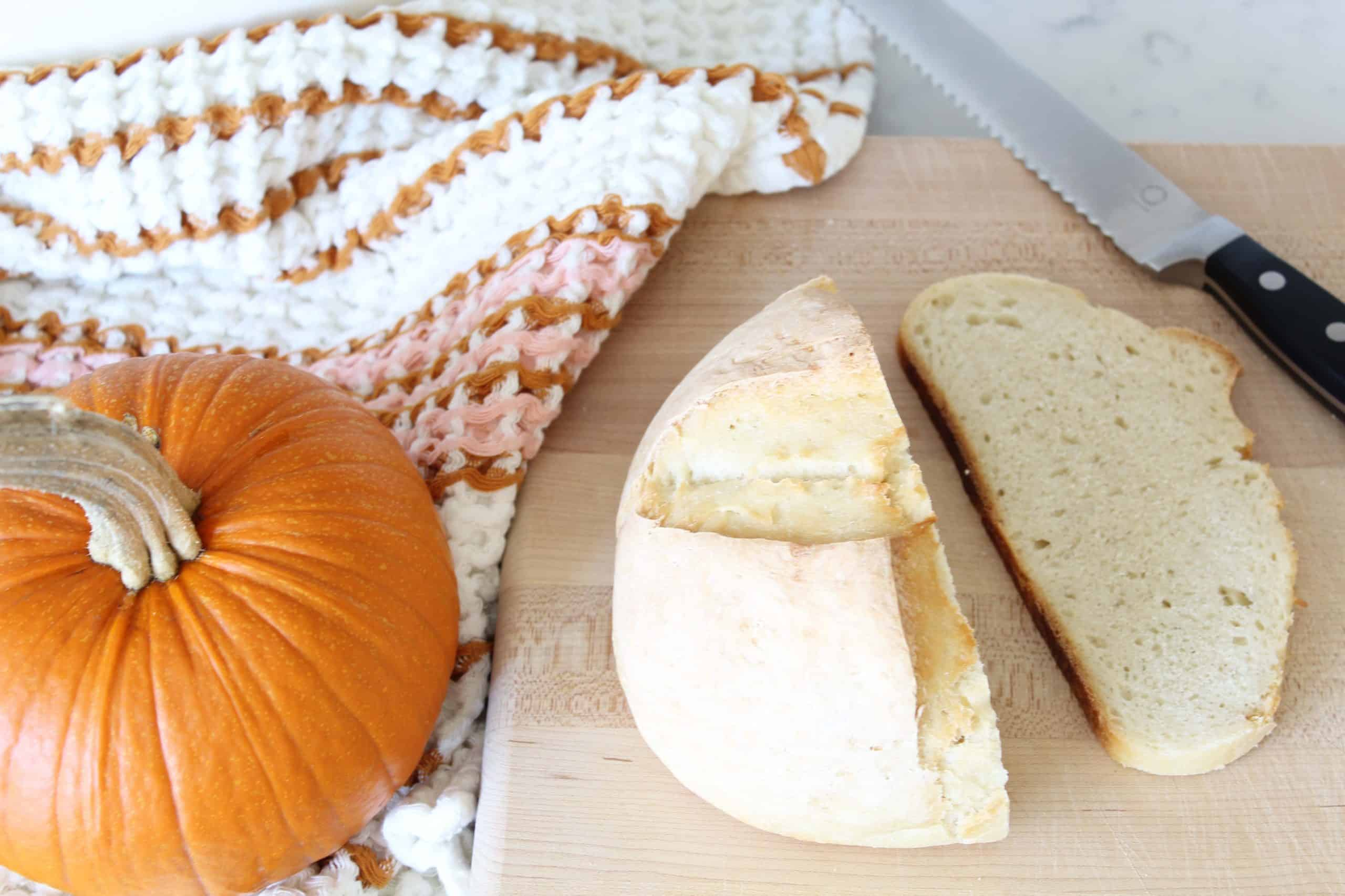 sourdough bread on bread board with pumpkin and anthropologie dish towel
