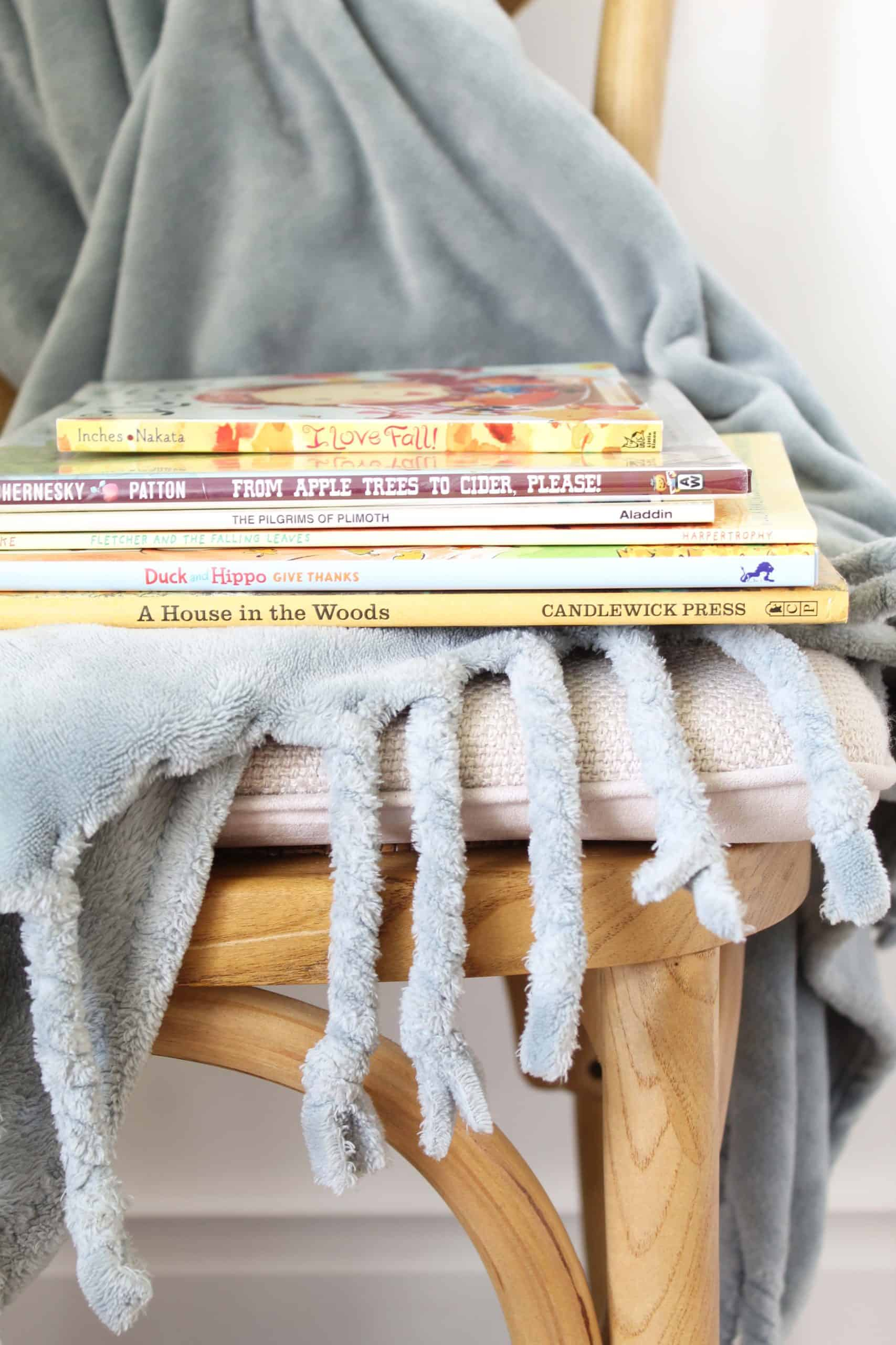 teal blanket with fall children's books on a farmhouse style chair