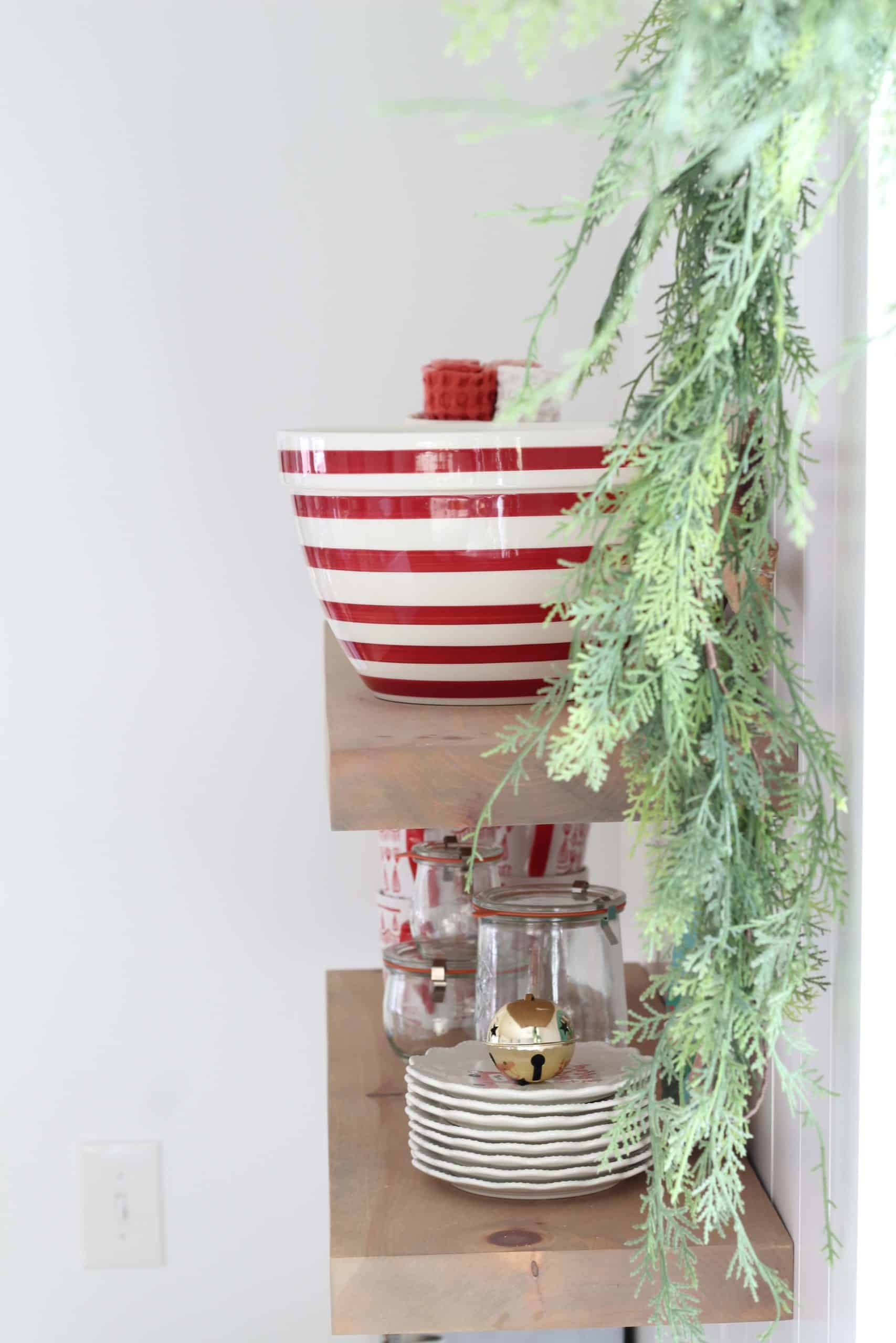 christmas garland around window, crate and barrel red striped bowl, open kitchen shelves