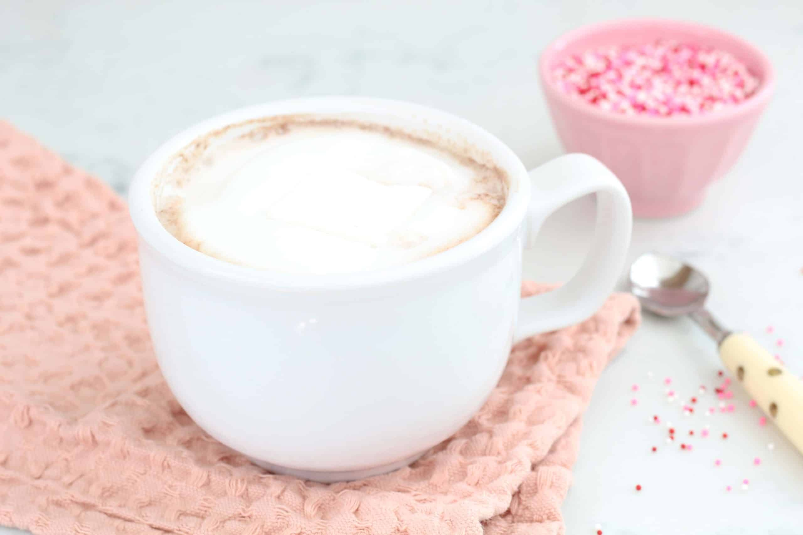 hot chocolate in white mug with pink sprinkles
