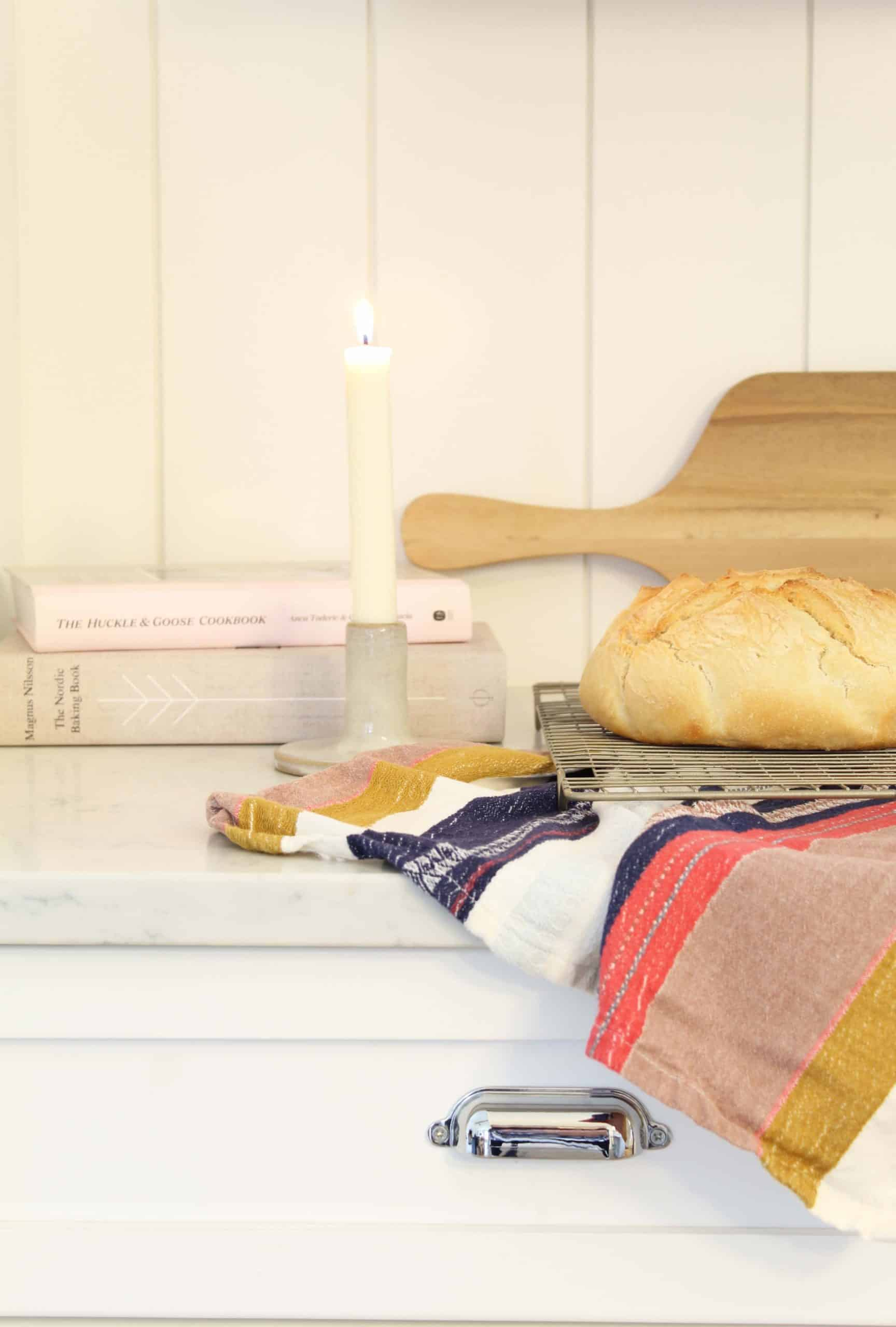 fresh sourdough bread, anthropologie kitchen towel, beeswax candle, huckle and goose cookbook