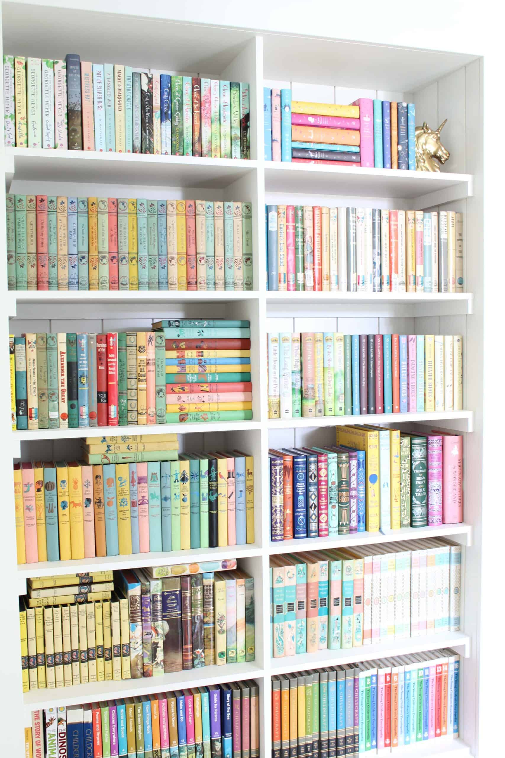 a closet converted into a bookshelf with colorful books and shiplap