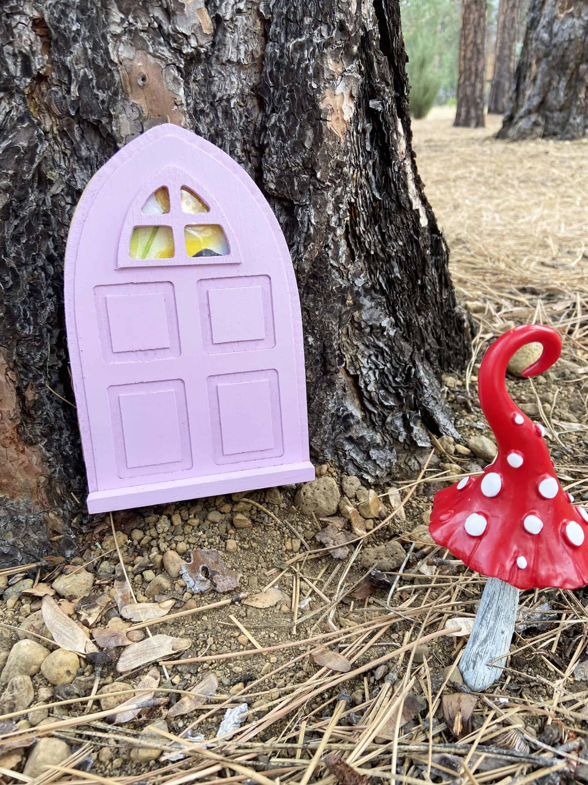 purple outdoor fairy door on a tree with red and white mushroom